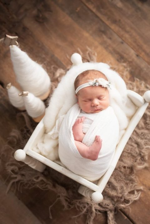 Newborn girl wrapped in white and surrounded by Christmas trees