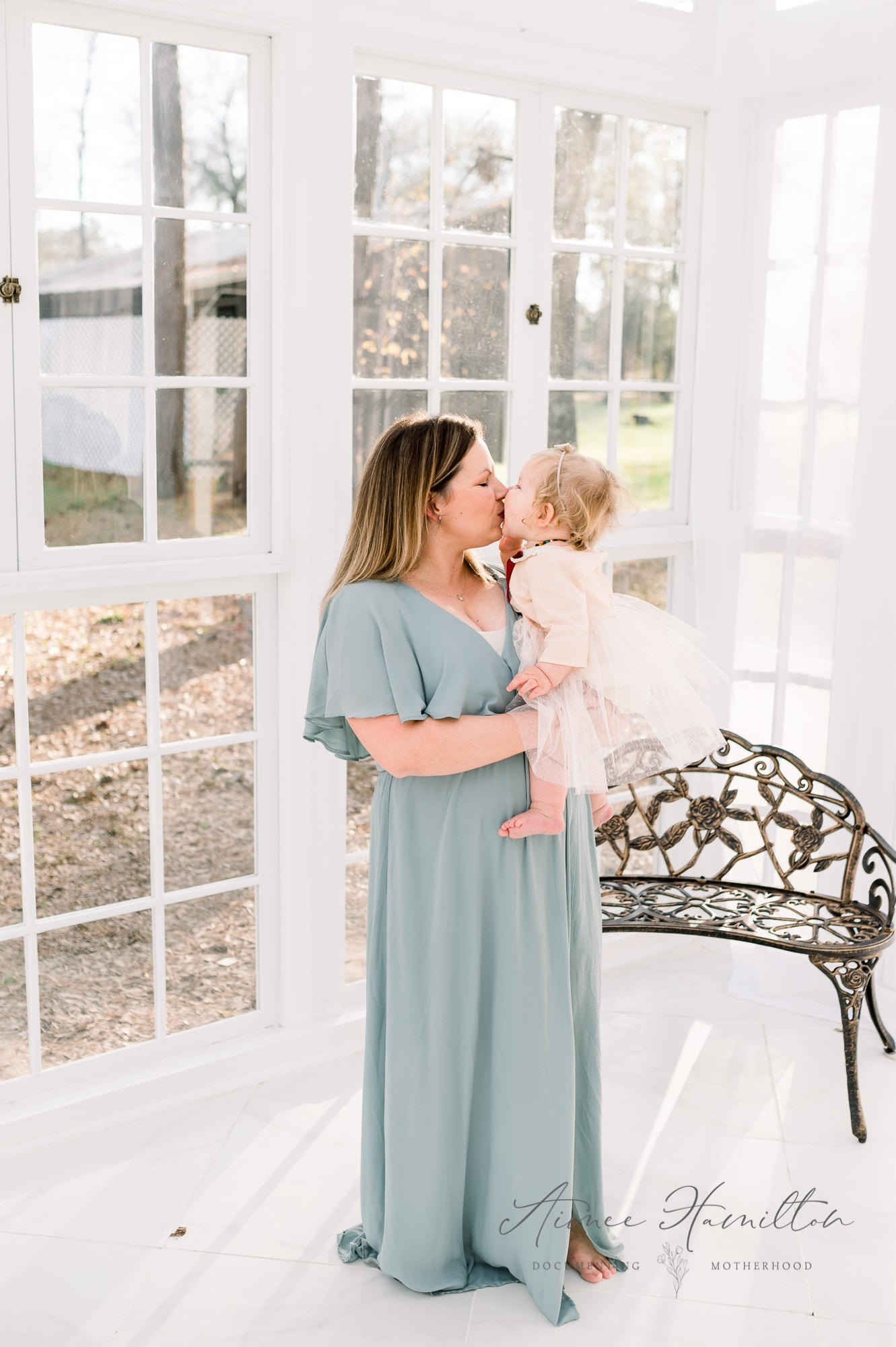 Baby kisses her mama in all white greenhouse