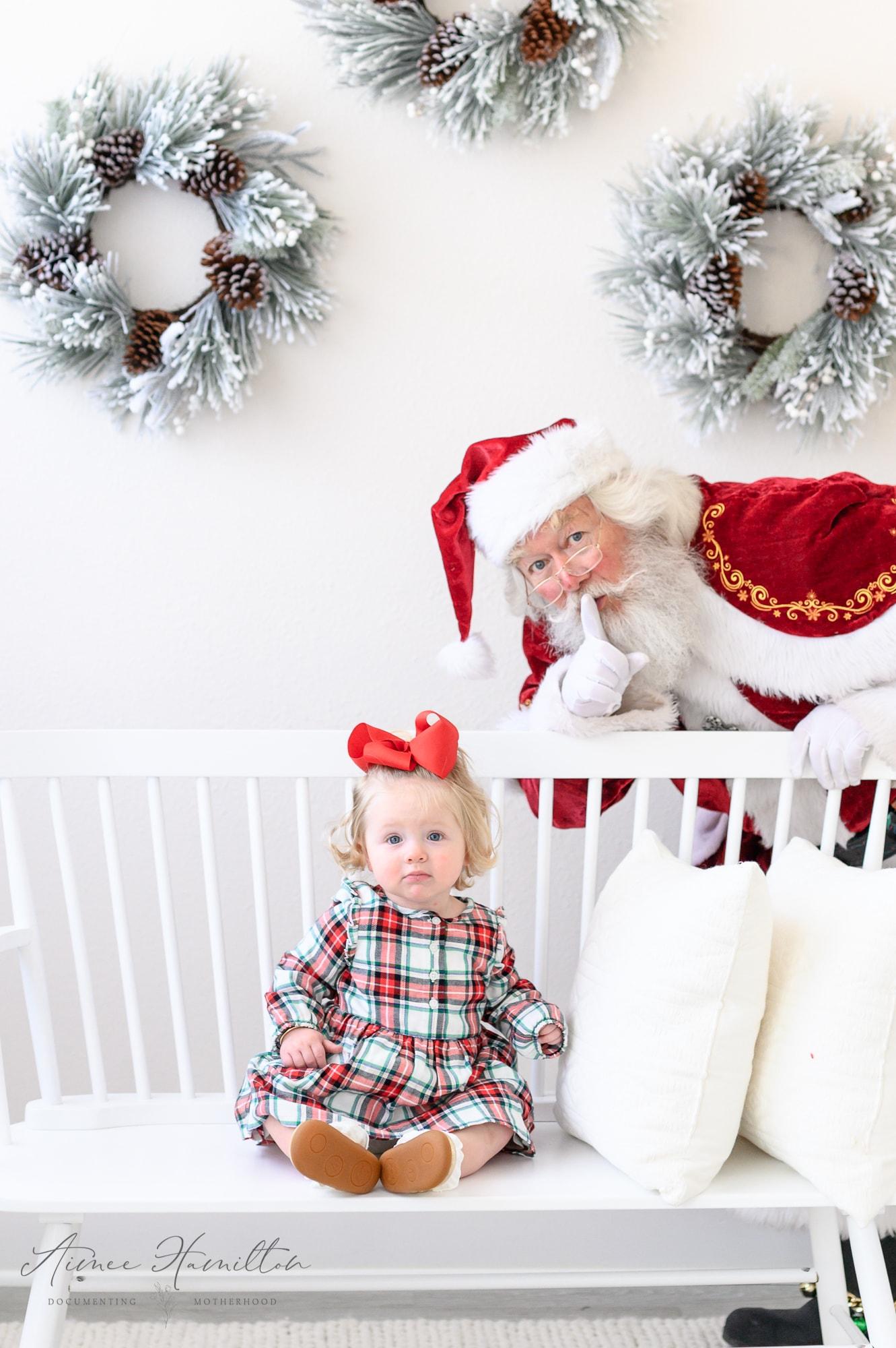 Santa hides behind baby