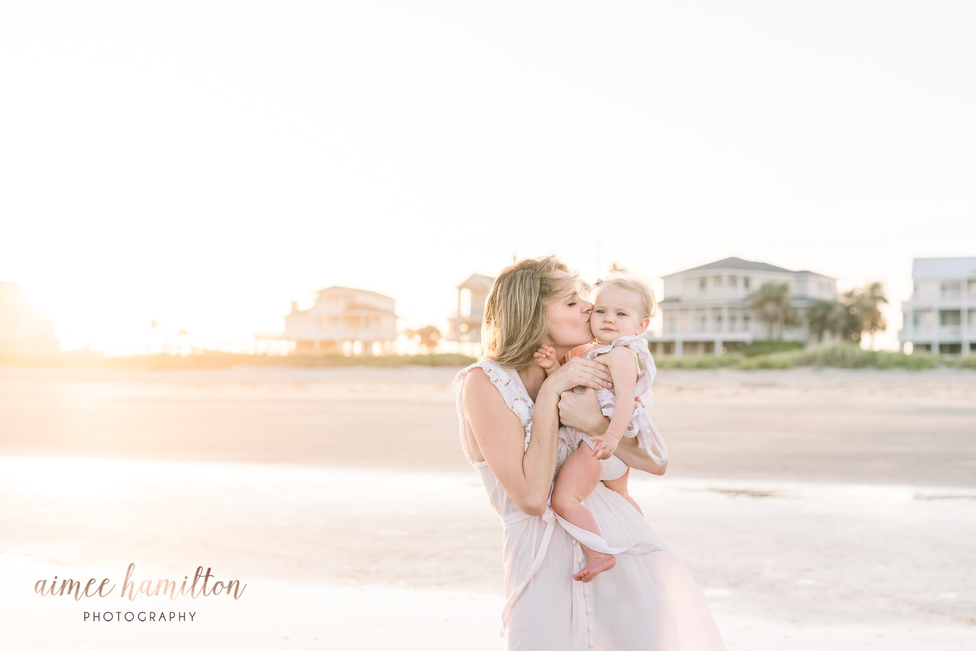 Mama kisses baby on the beach in Galveston