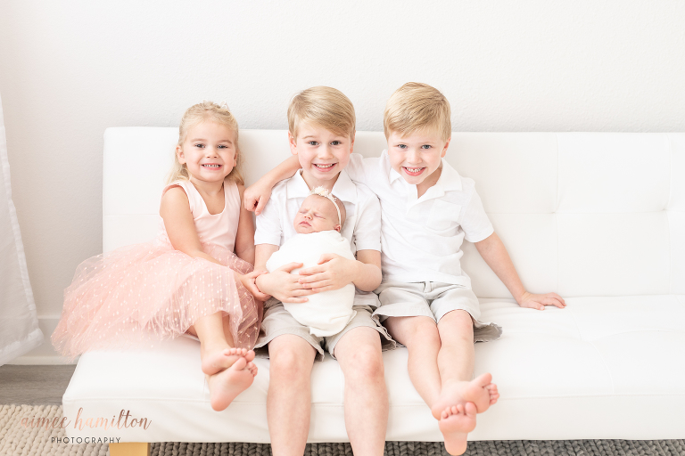 Siblings pose with brand new baby sister in all white newborn studio