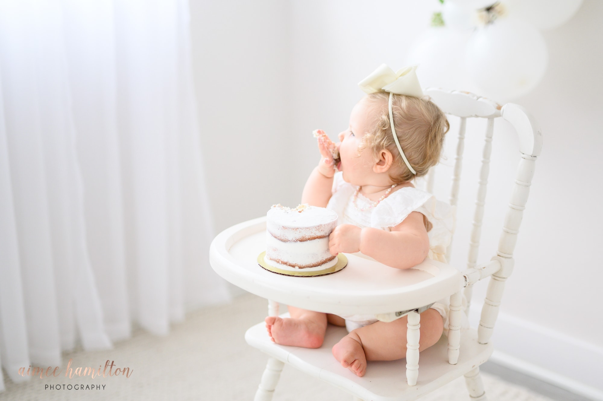 baby eating cake in white high chair