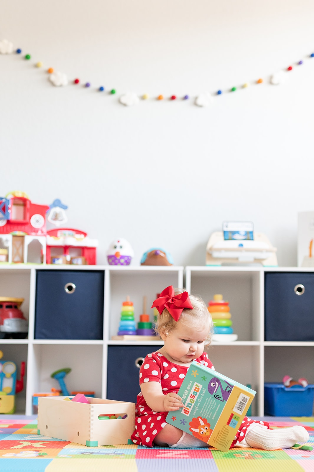 Toddler Girl playing with toys in colorful playroom