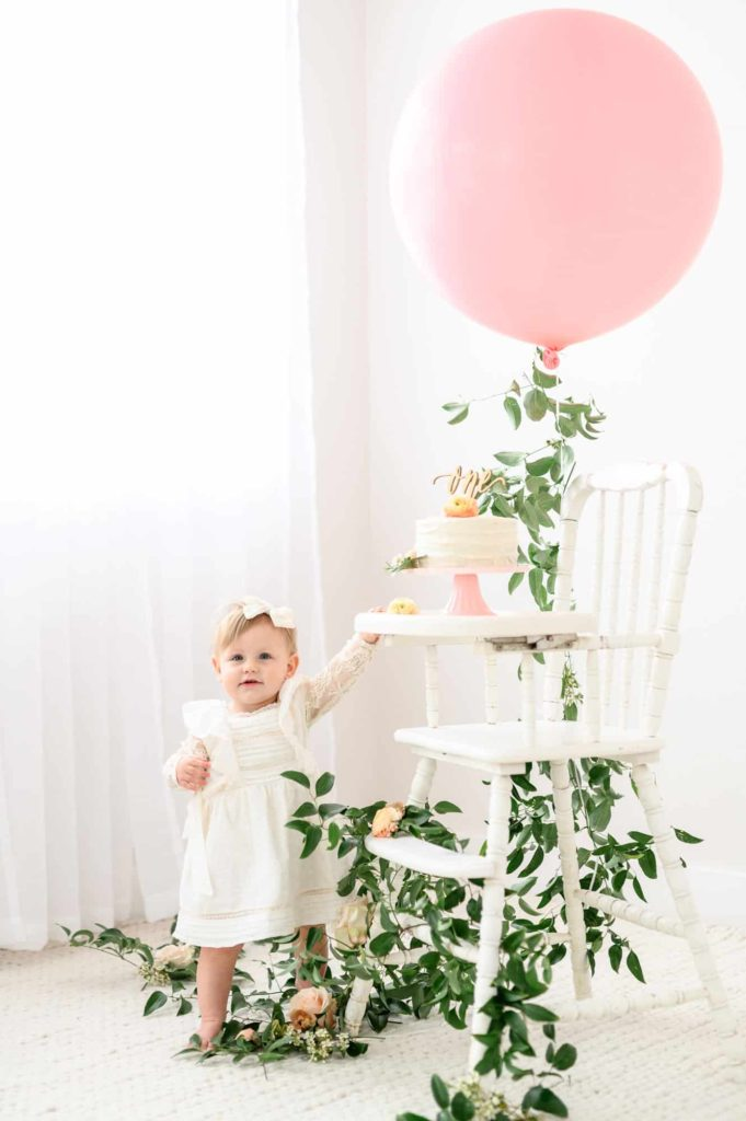 baby with antique high chair and balloon