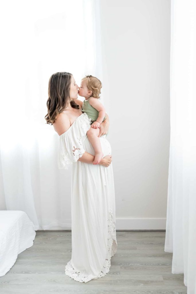 Mom kissing baby maternity session