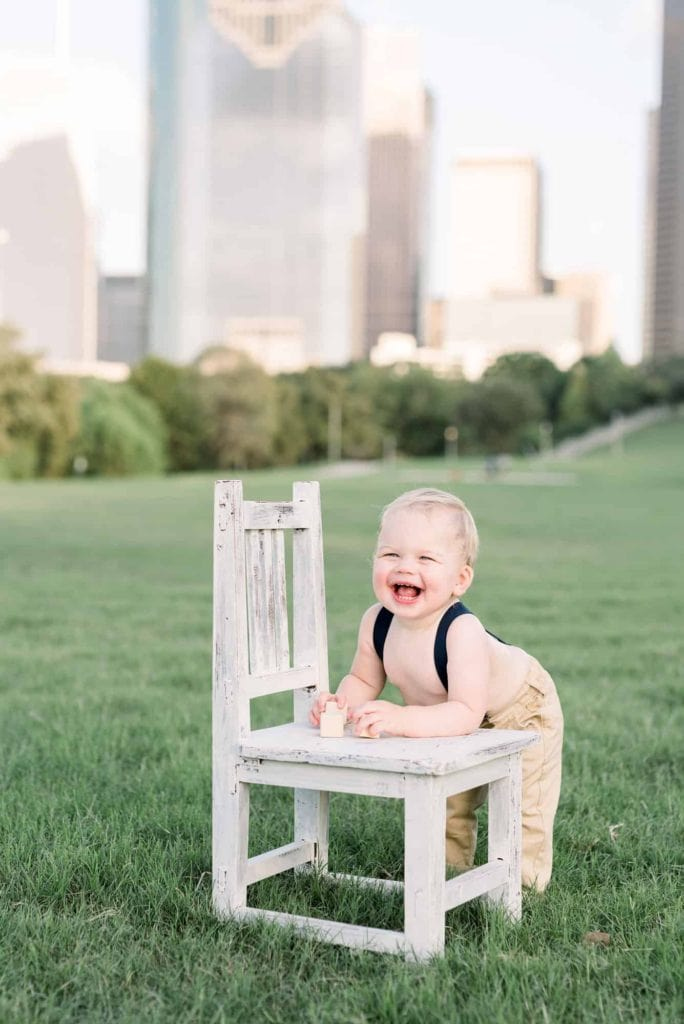 Baby with chair in front of Dallas skyline