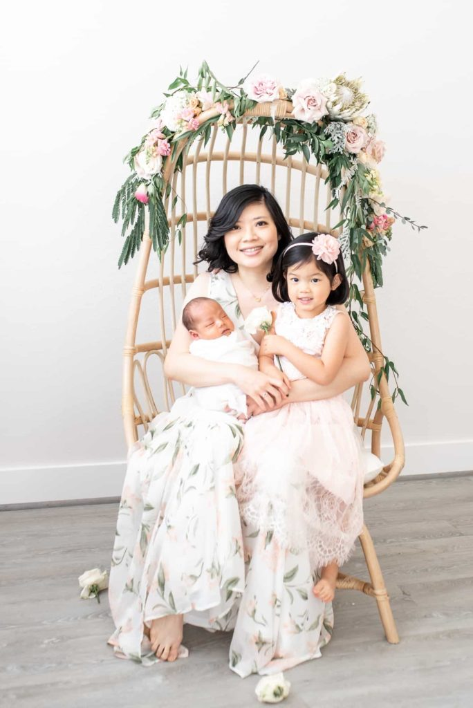 Mom and kids in wicker chair with florals