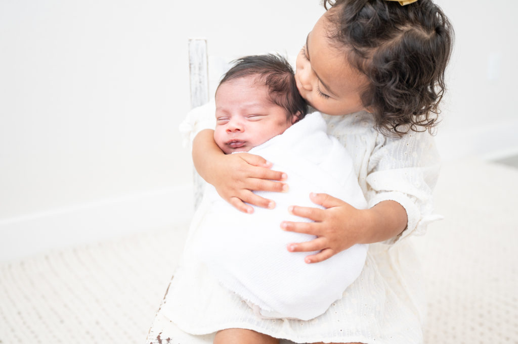 Sister holds newborn brother