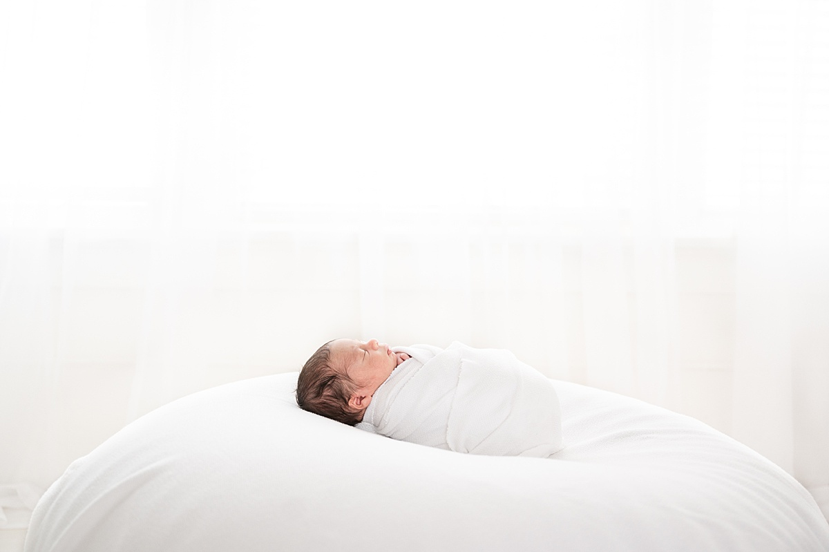 Backlit image of baby in classic white swaddle by Highland Park Newborn Photographer, Aimee Hamilton Photography.