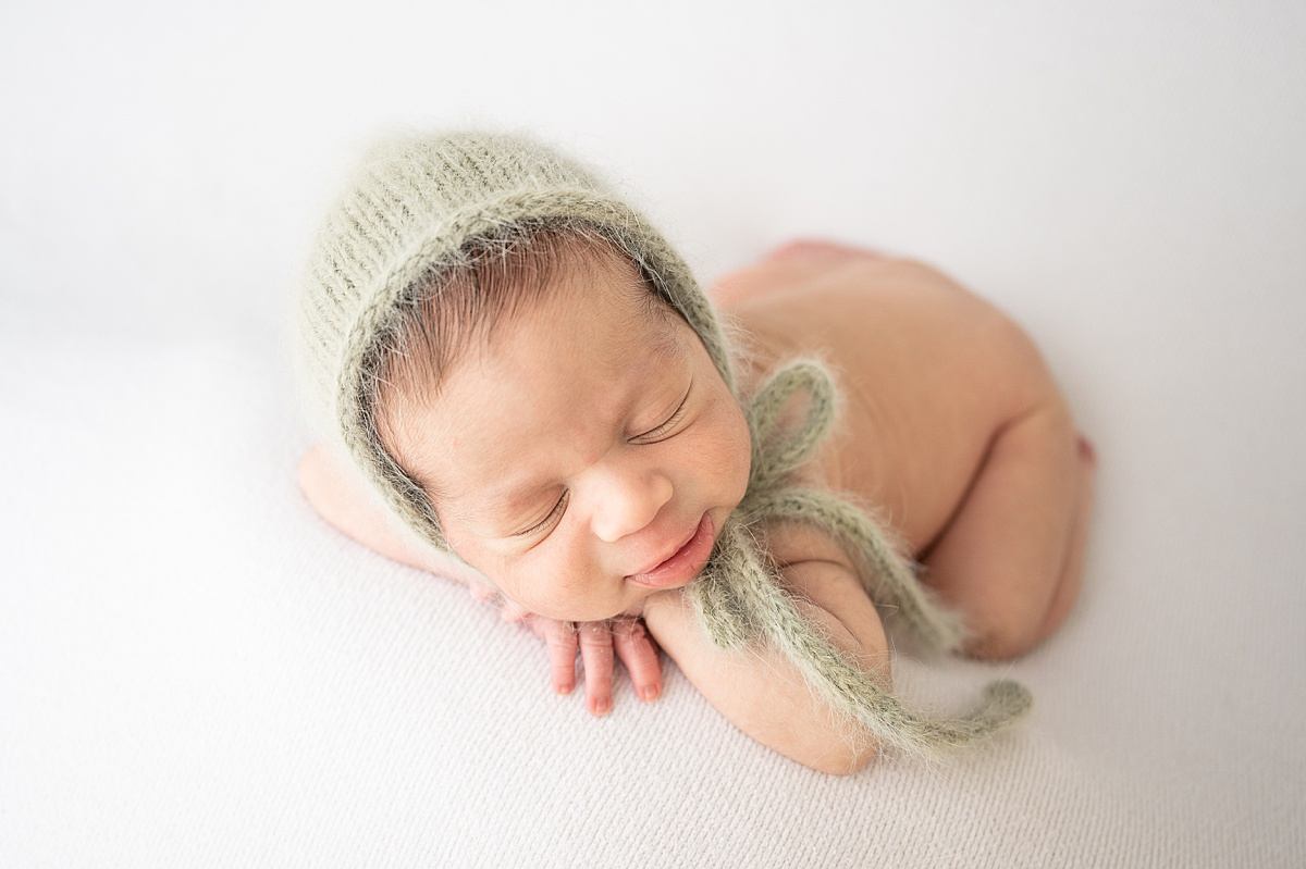 Sleeping baby wearing sage knit bonnet. Photo by Highland Park Newborn Photographer, Aimee Hamilton Photography.