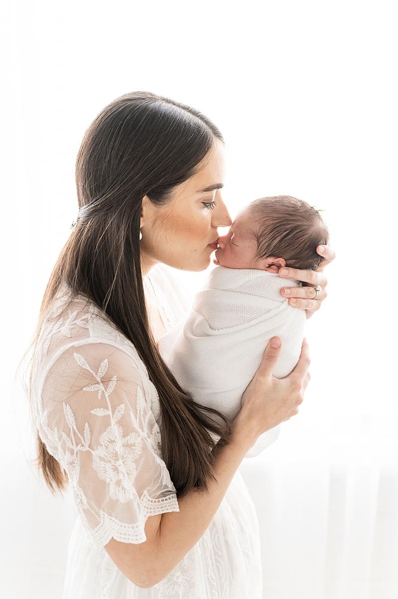 Mom kissing baby during studio newborn session by Highland Park Newborn Photographer, Aimee Hamilton Photography.