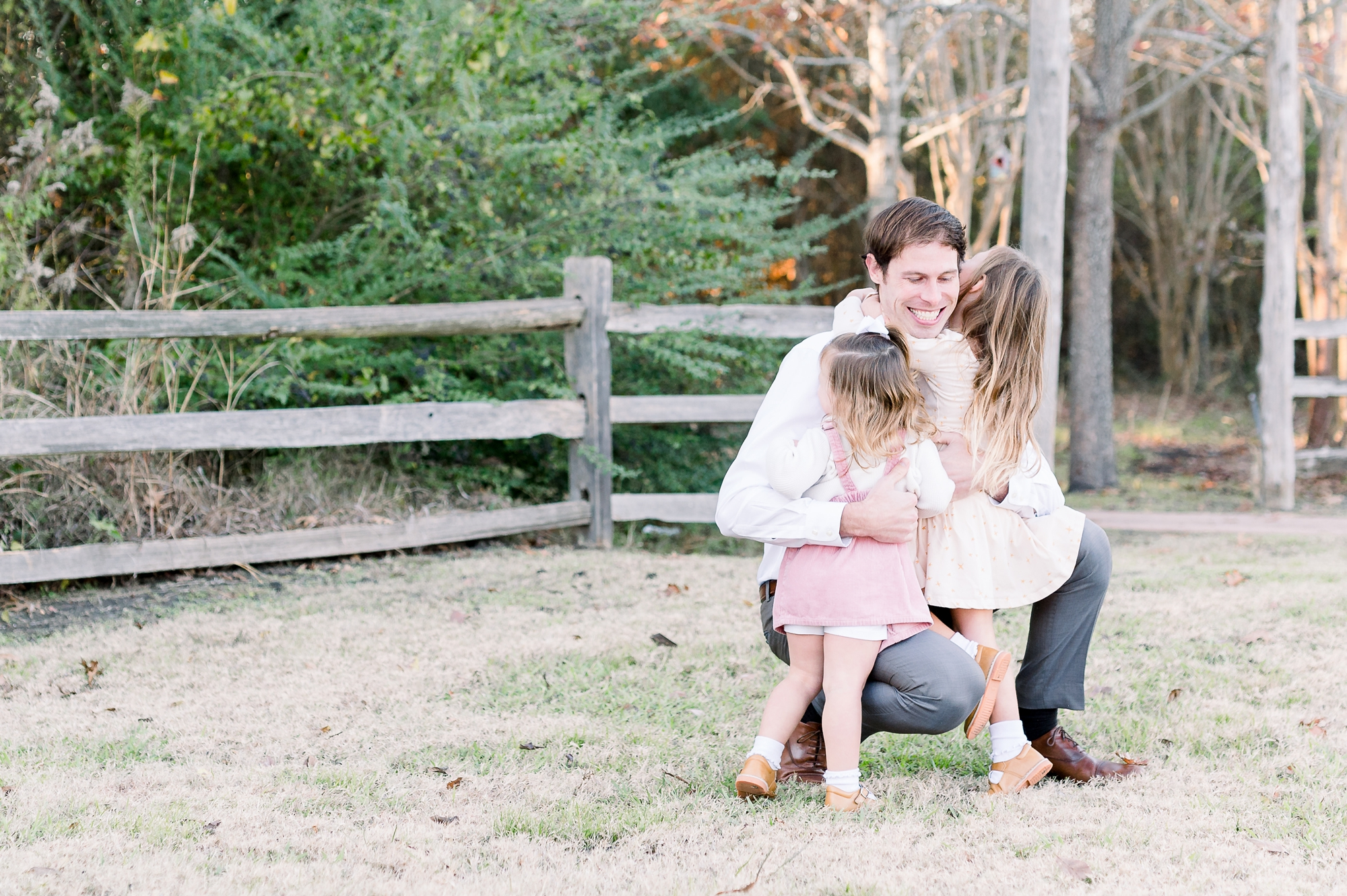 Dad sitting with daughters during family session at McKinney park. Image by Aimee Hamilton Photography.