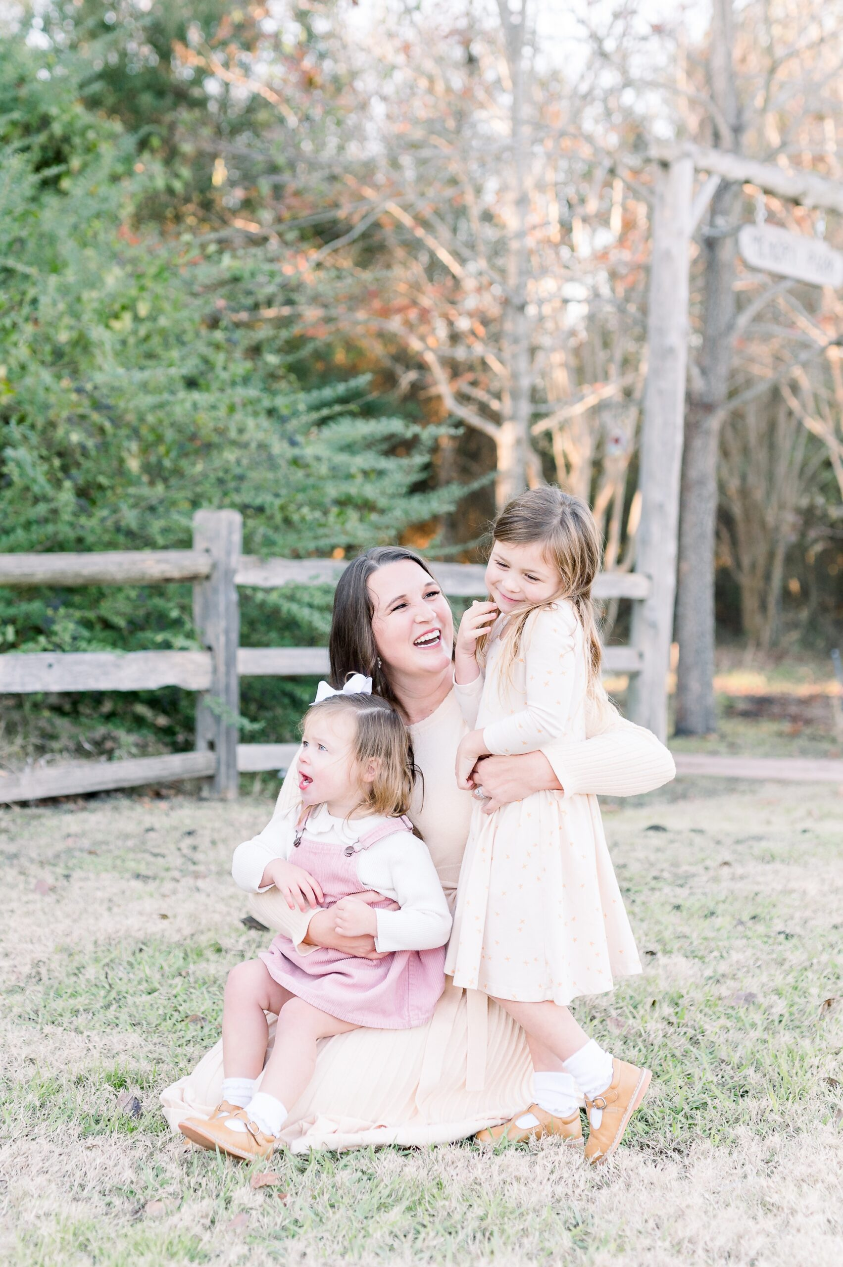 Sweet photo of Mom sitting with two daughters in McKinney family photography session. Photo by Aimee Hamilton Photography.