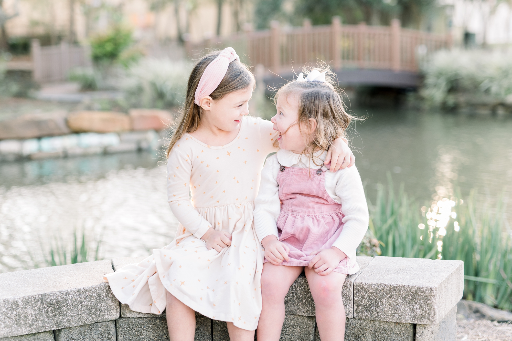 Sisters looking at each other with arms around each other. Photo by Aimee Hamilton Photography.