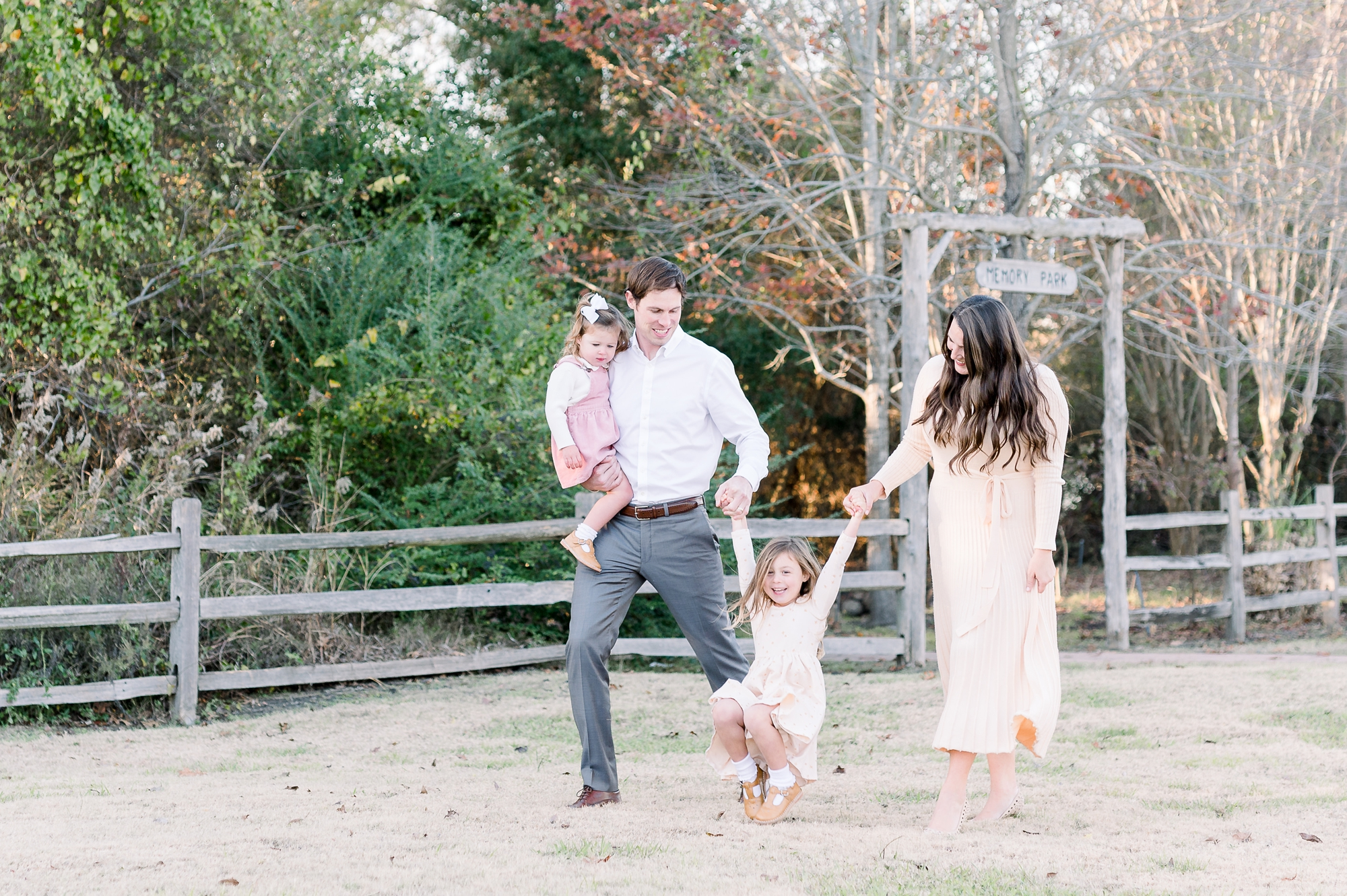 Family walking with child swinging in the middle during family portrait session. Photo by Aimee Hamilton Photography.