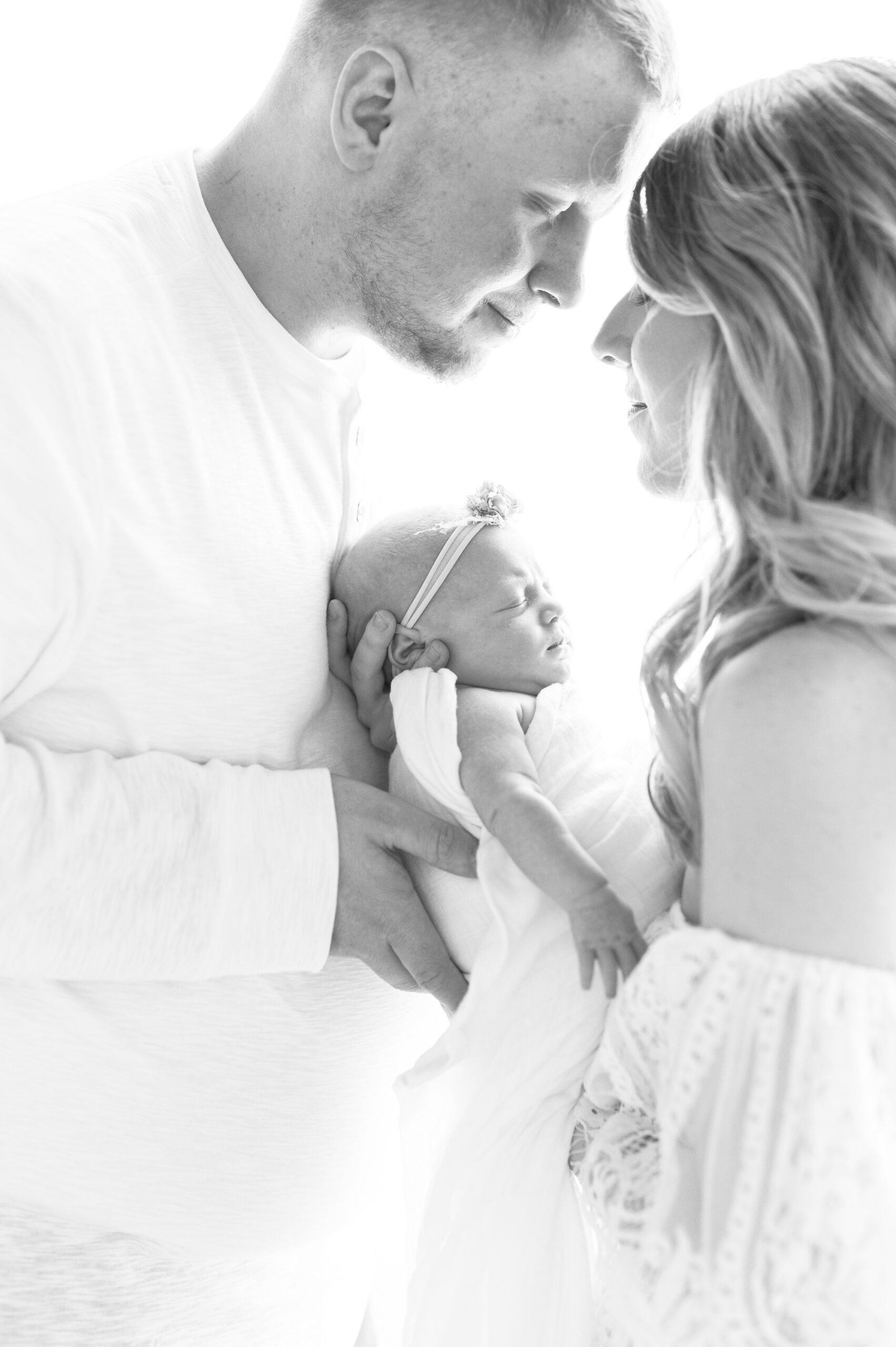 Backlit image of parents holding newborn during studio session with Aimee Hamilton Photography.