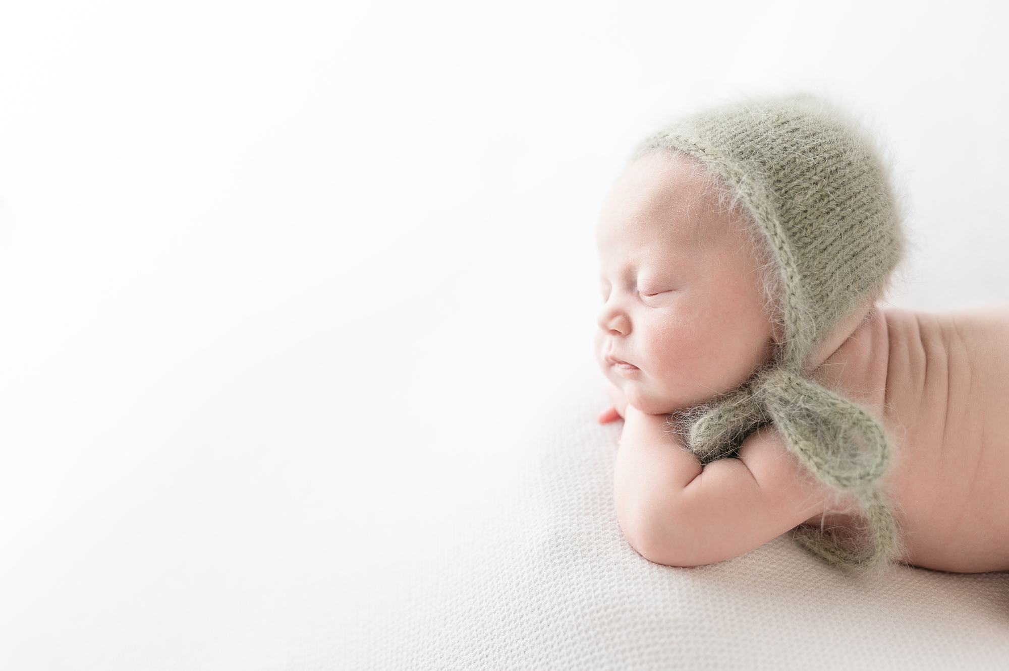 Posed baby girl in knit bonnet during studio newborn photography session. Photo by Aimee Hamilton Photography.