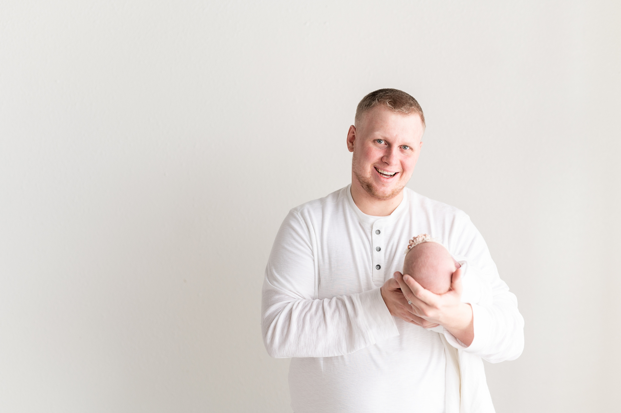 Dad holding baby girl and smiling at camera during session with Aimee Hamilton Photography.