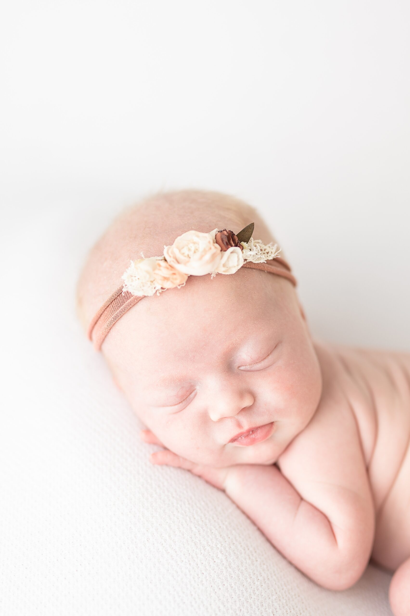Image of baby with headband in studio newborn session. Photo by Aimee Hamilton Photography.
