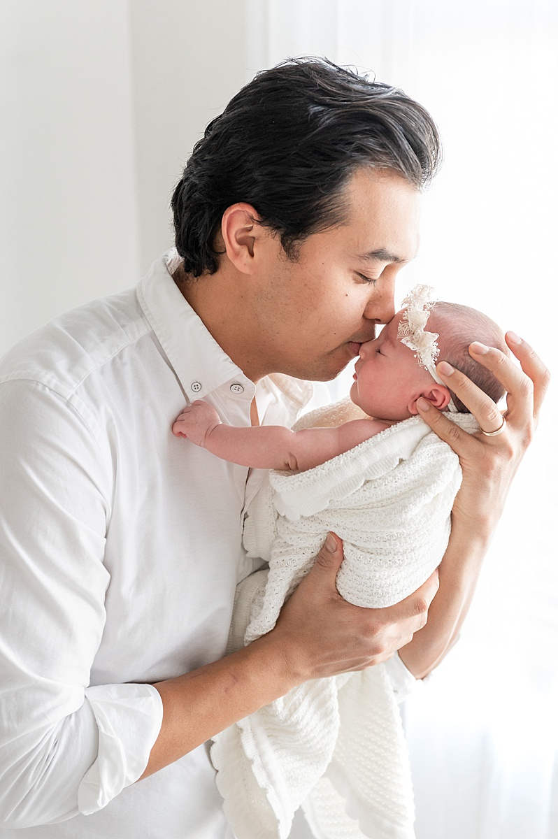 Backlit image of dad kissing baby girl in McKinney newborn photography studio. Image by Aimee Hamilton Photography.