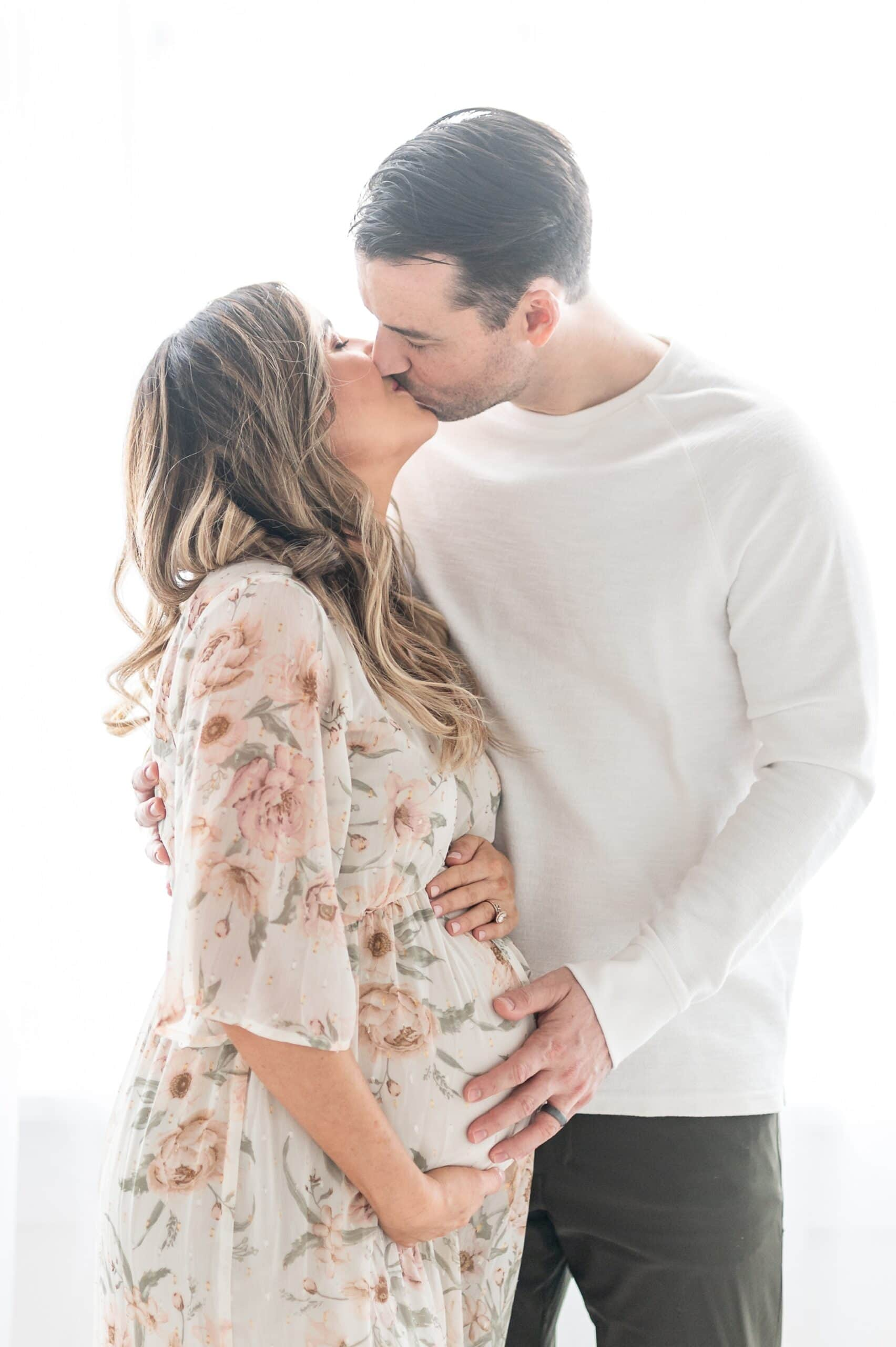Expecting parents kiss in front of a window during maternity session in studio. Photo by Aimee Hamilton Photography.