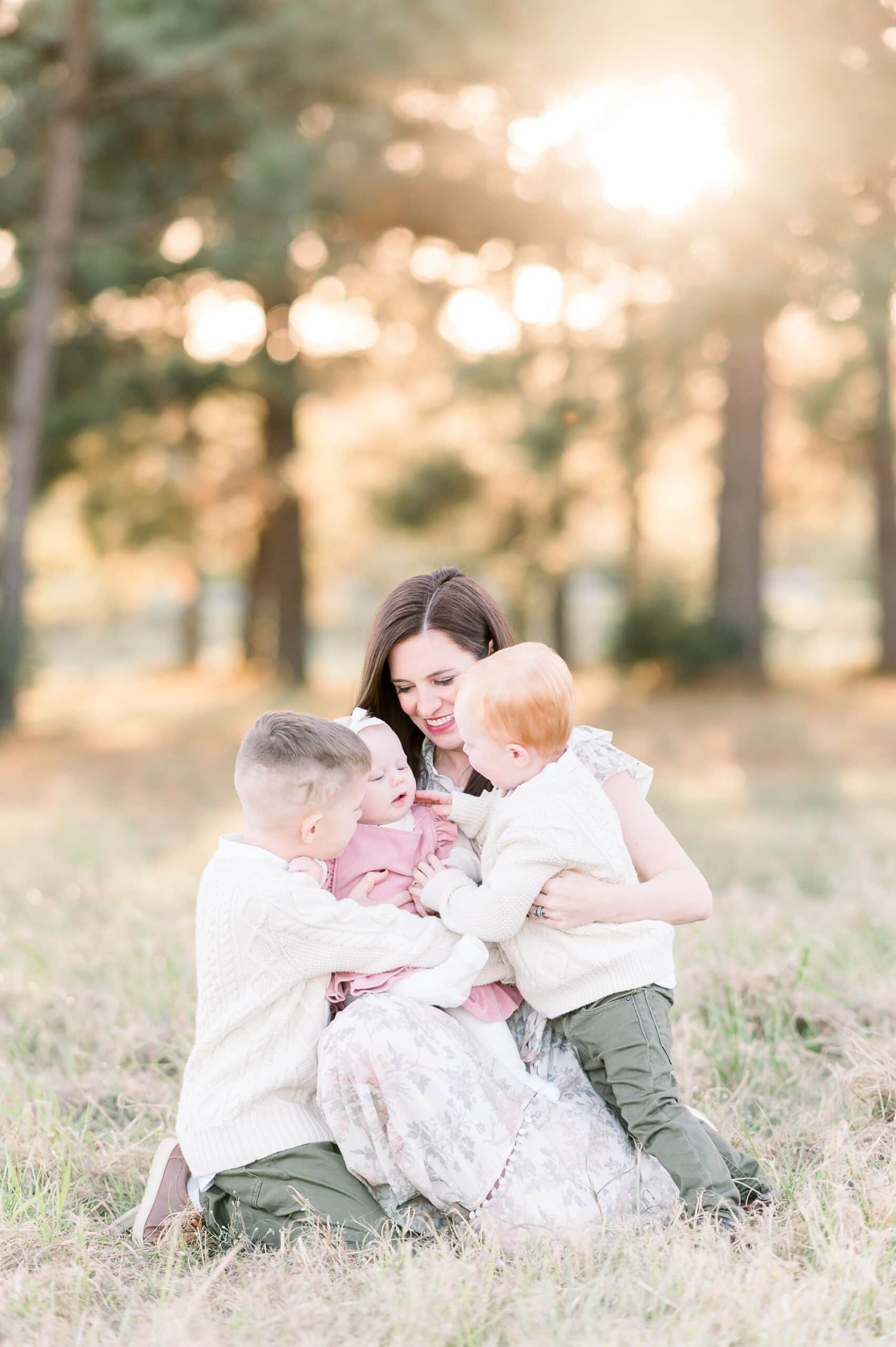 Sweet moment with Mom and three children sitting on the grass during family session. Photo by Aimee Hamilton Photography.