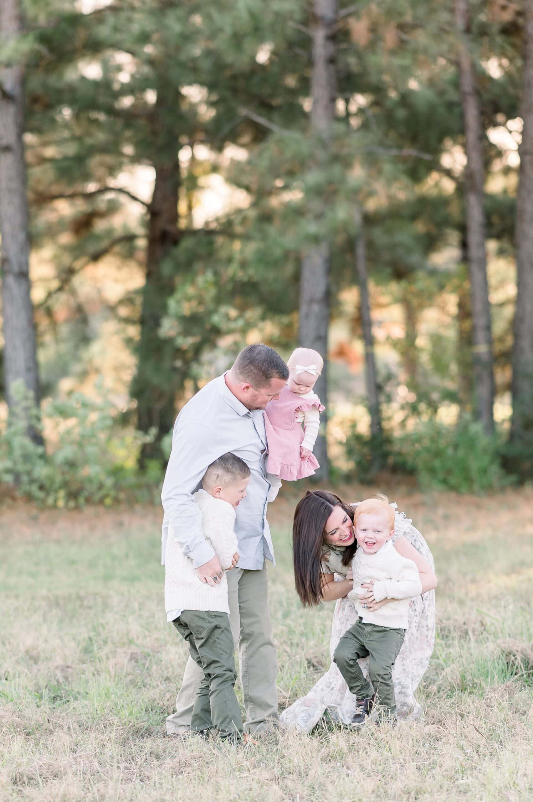 Mom and Dad hugging toddlers during family session. Photo by Aimee Hamilton Photography.