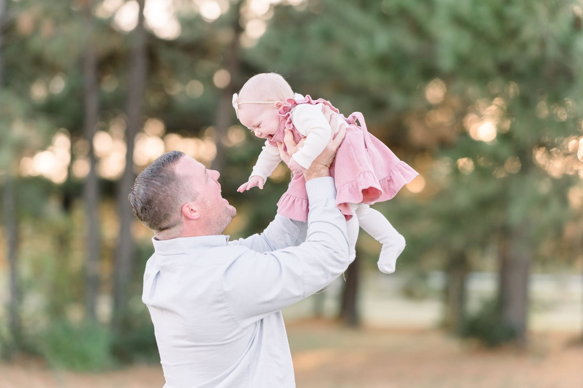 Dad playing airplane with daughter during session. Photo by Dallas TX family photographer, Aimee Hamilton Photography.