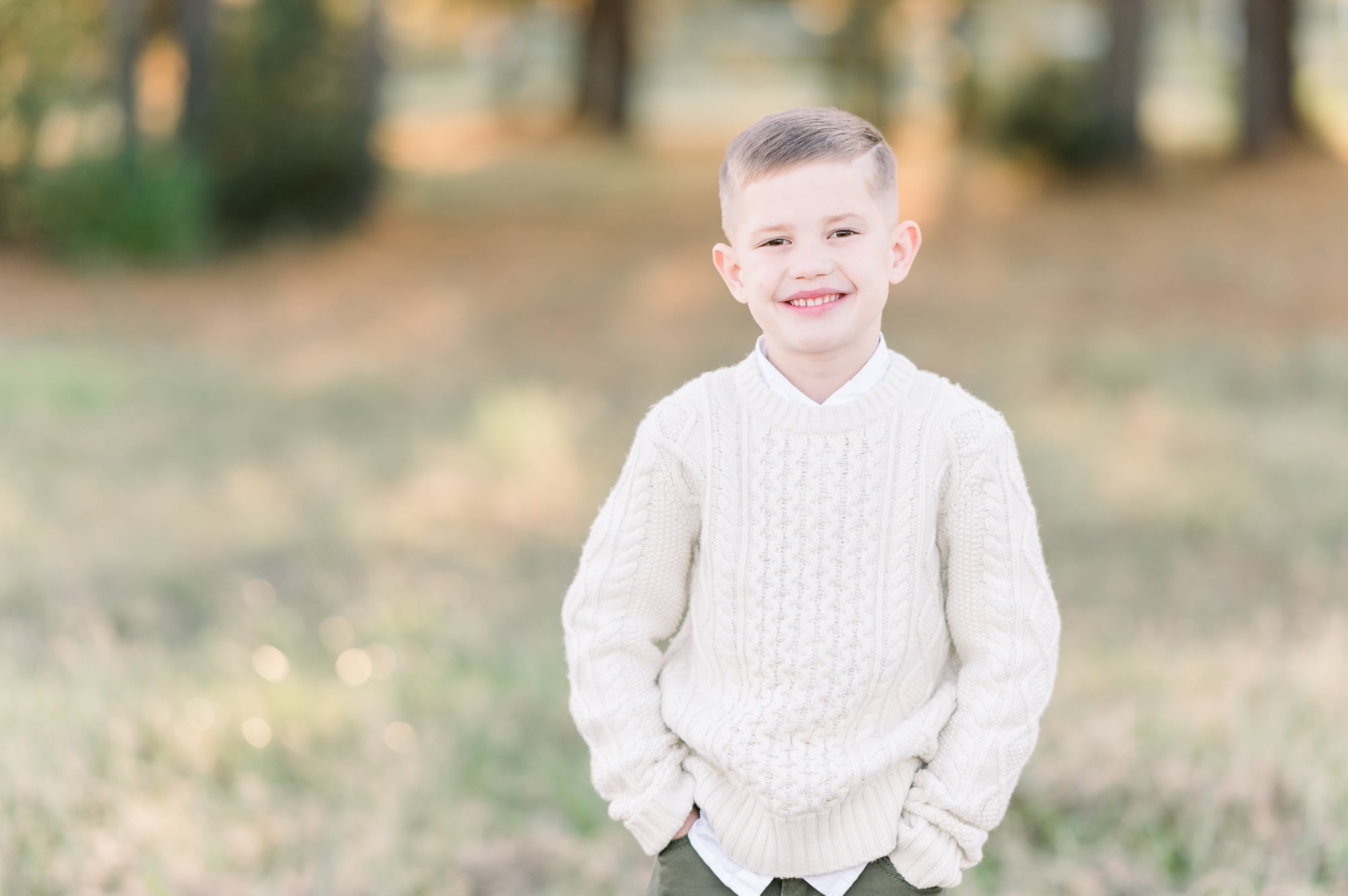 Oldest son in cable knit sweater smiling at camera during family session. Photo by Aimee Hamilton Photography.