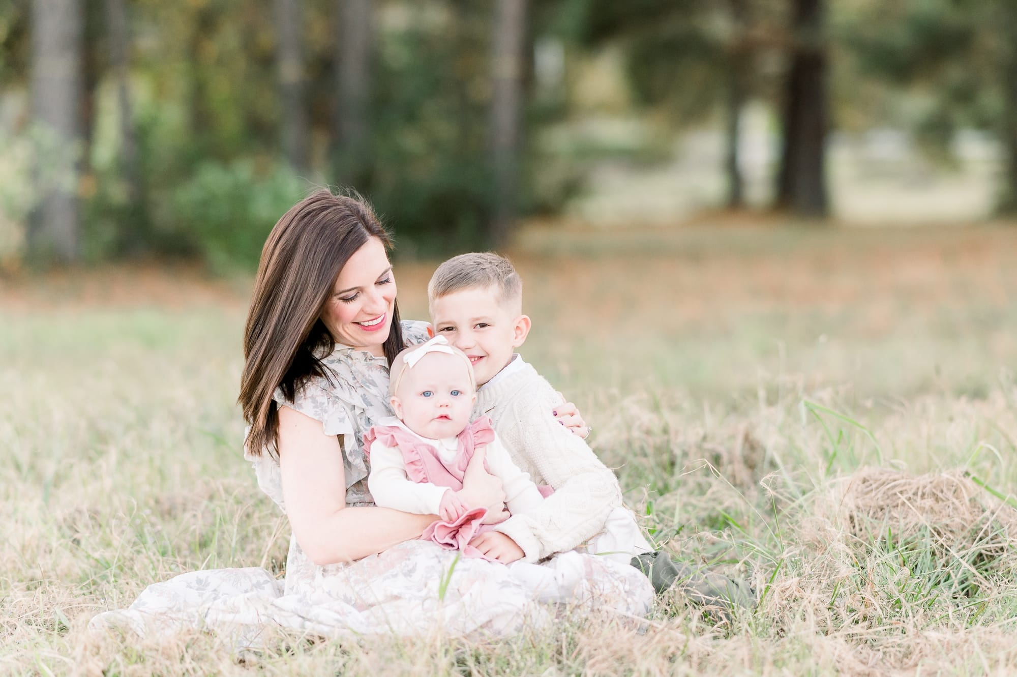 Mom sitting in grass with two kids during Fall family session outside of Dallas TX. Photo by Aimee Hamilton Photography.