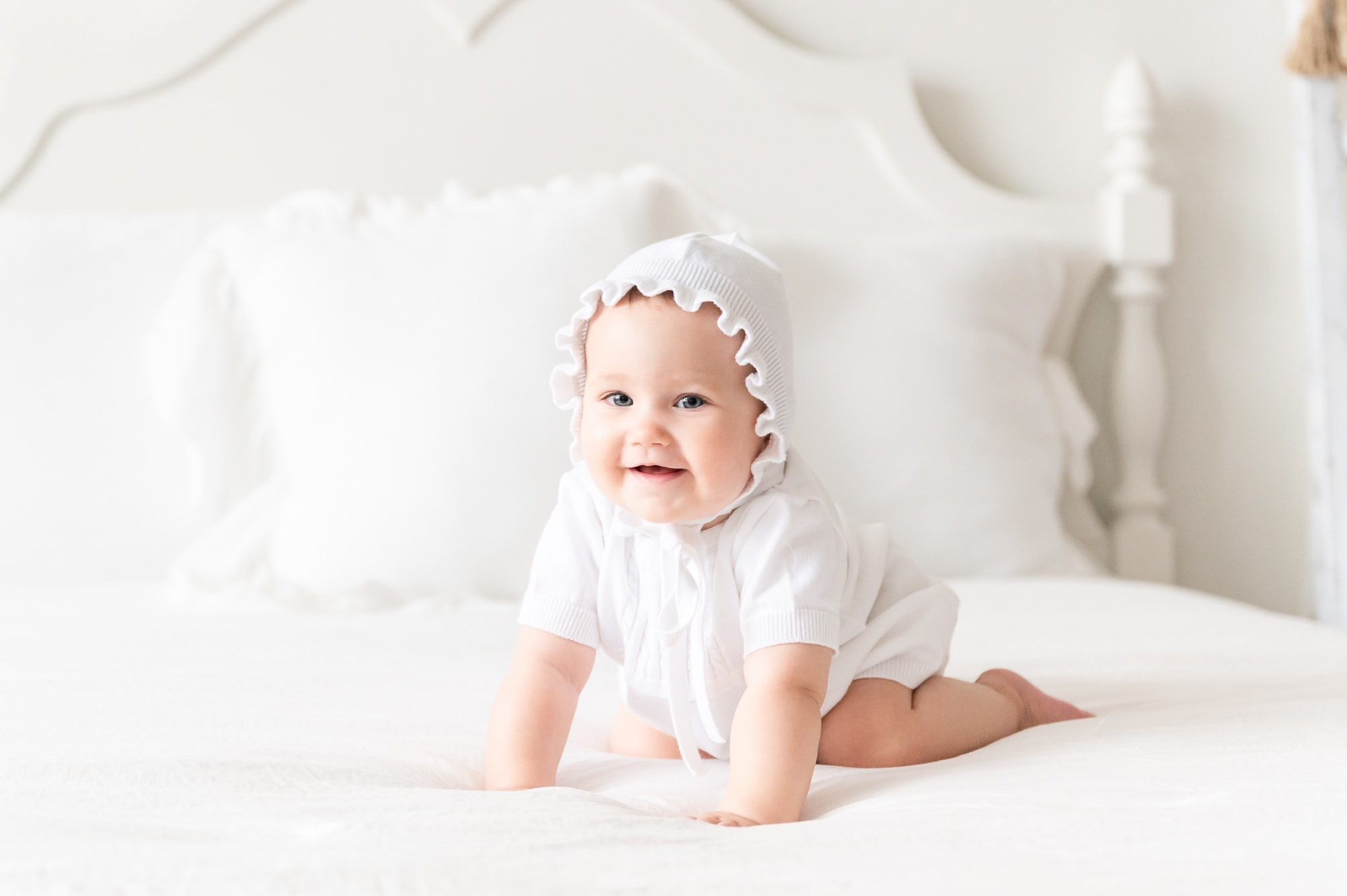 Baby girl wearing white bonnet and knit set during milestone session. Photo by Aimee Hamilton Photography