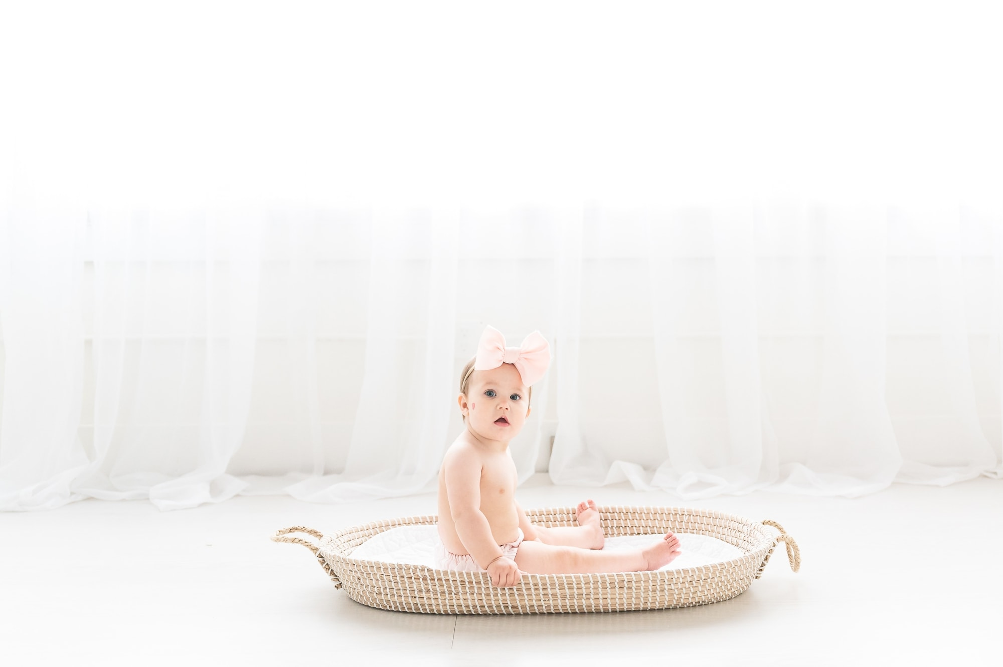 6 month old photo shoot with baby sitting in Moses basket in studio. Photo by Aimee Hamilton Photography