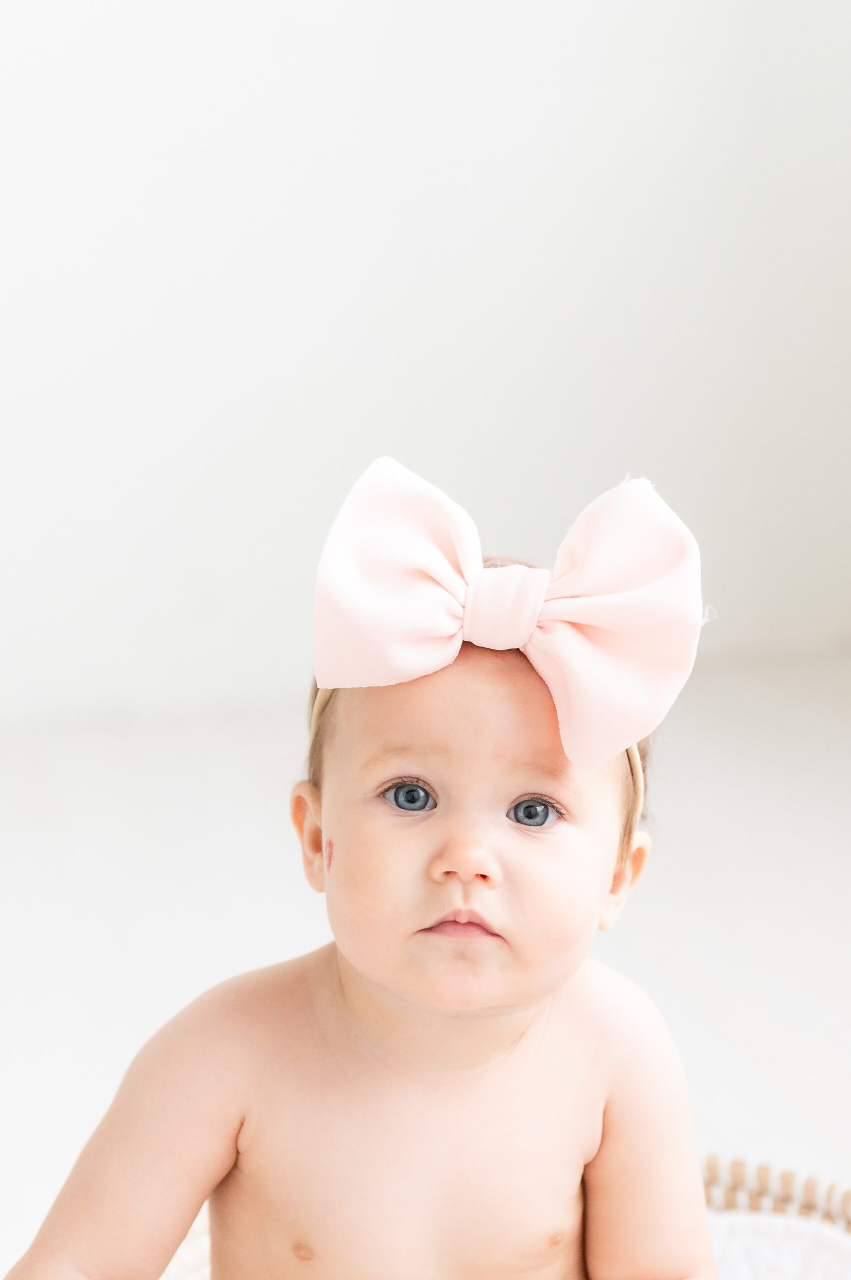 Closeup of baby with pink bow and pretty blue eyes. Photo by Aimee Hamilton Photography