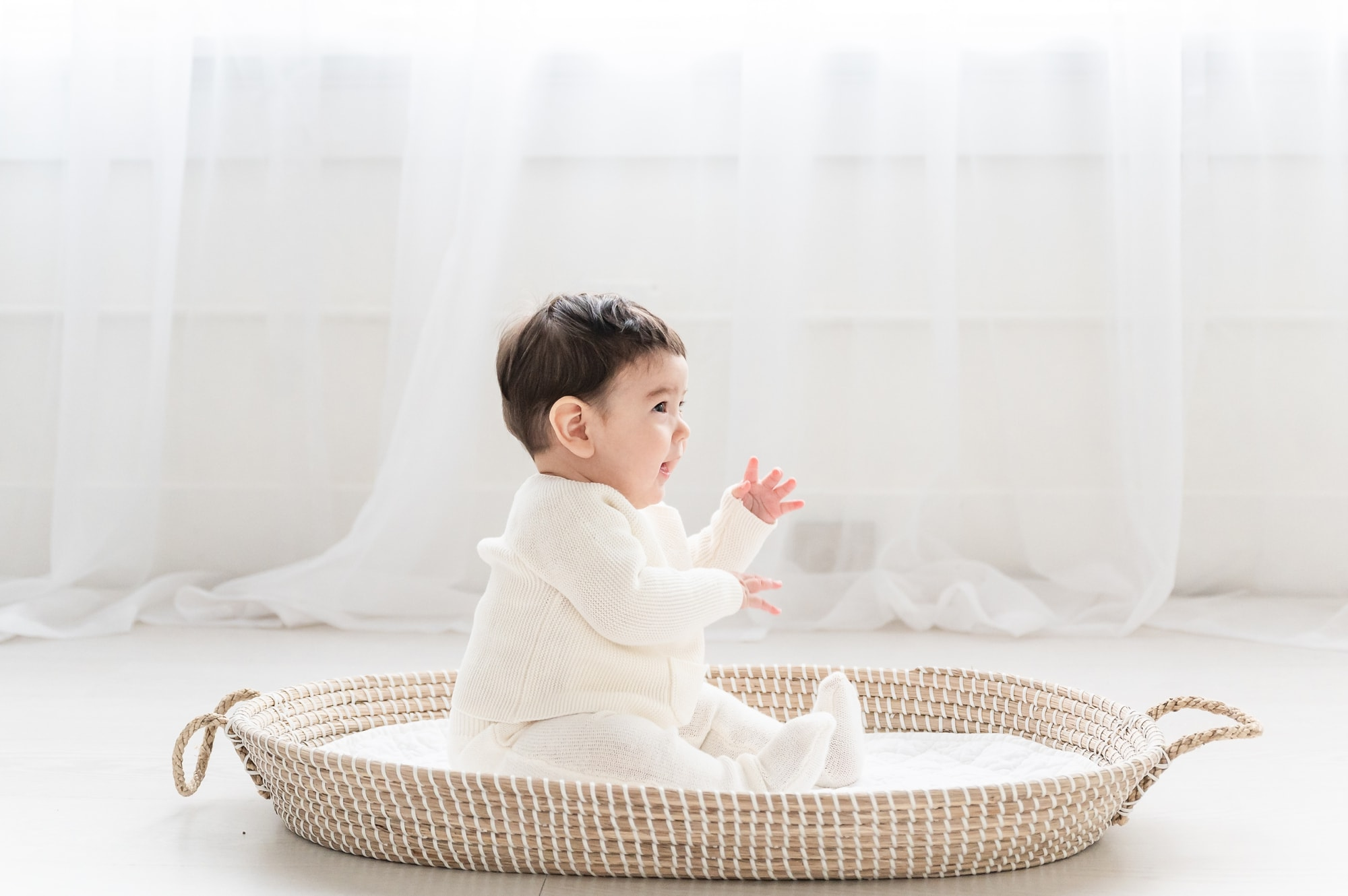 6 month old photo shoot with baby boy sitting in Moses basket. Photo by Aimee Hamilton Photography