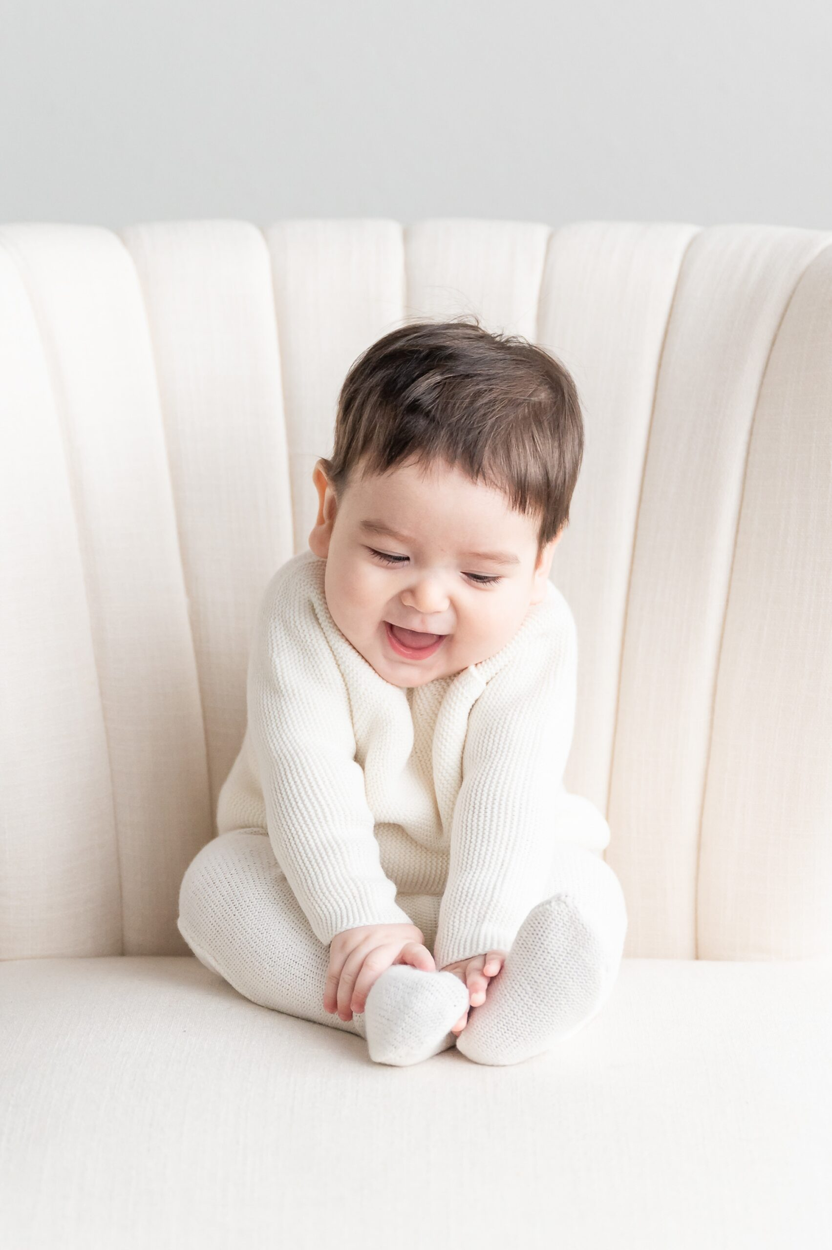 Laughing baby on white chair during studio session. Photo by Dallas baby photographer, Aimee Hamilton Photography