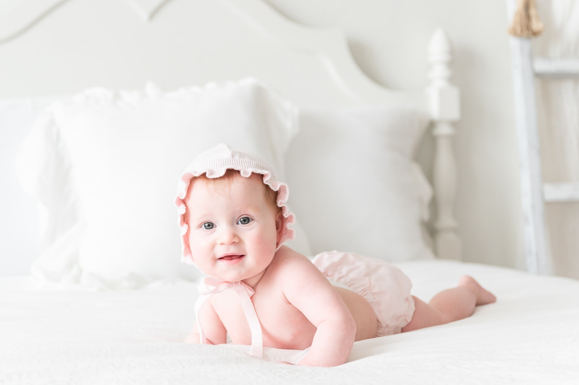 Baby girl wearing bonnet and diaper cover on bed in studio during milestone session. Photo by Aimee Hamilton Photography