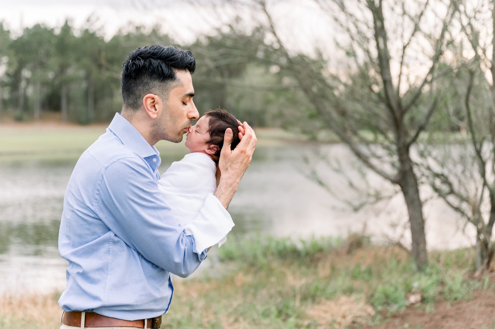 Dad kissing baby's nose during outdoor newborn session. Photo by Frisco newborn photographer, Aimee Hamilton Photography.