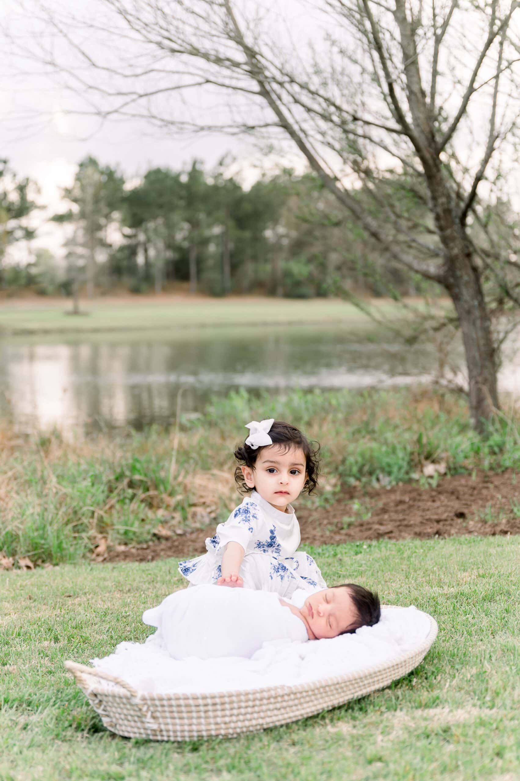 Big sister sitting next to baby brother during outdoor newborn session in Frisco. Photo by Aimee Hamilton Photography.
