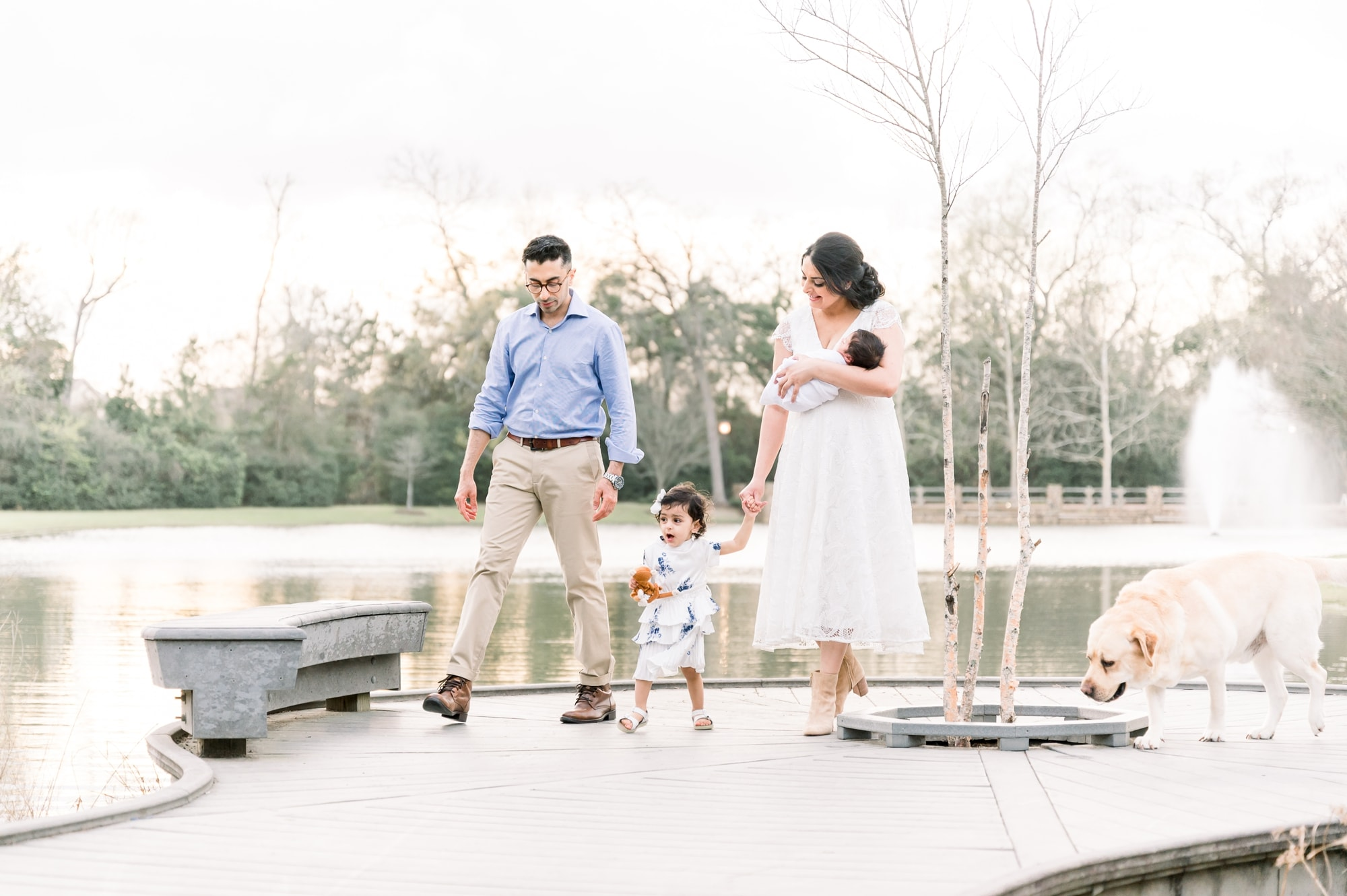 Mom, Dad and toddler walking while Mom holds baby in Frisco, TX park. Photo by Aimee Hamilton Photography.