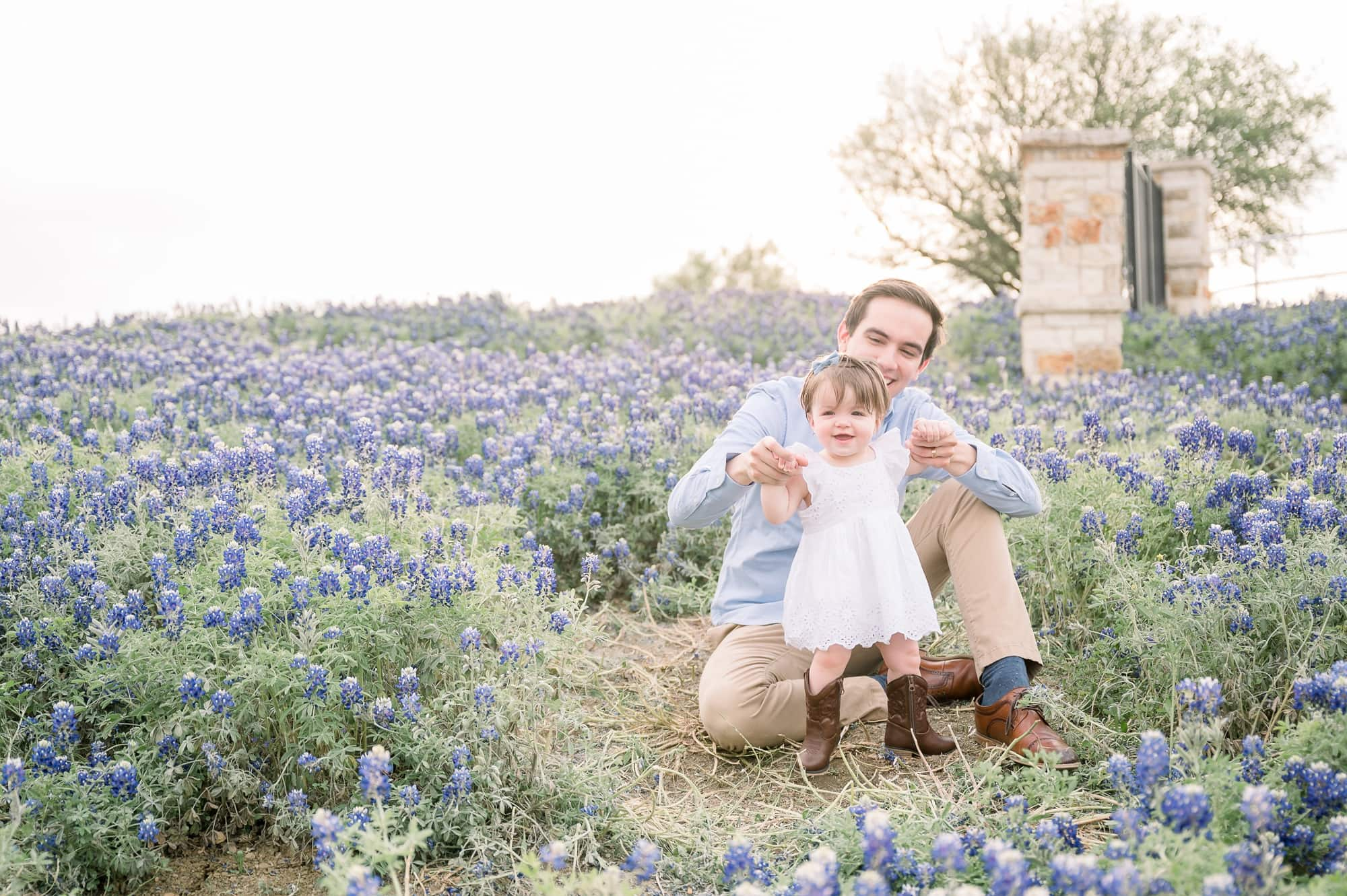 Dad holding baby girl's hands while she stands in bluebonnet field. Photo by Aimee Hamilton Photography.