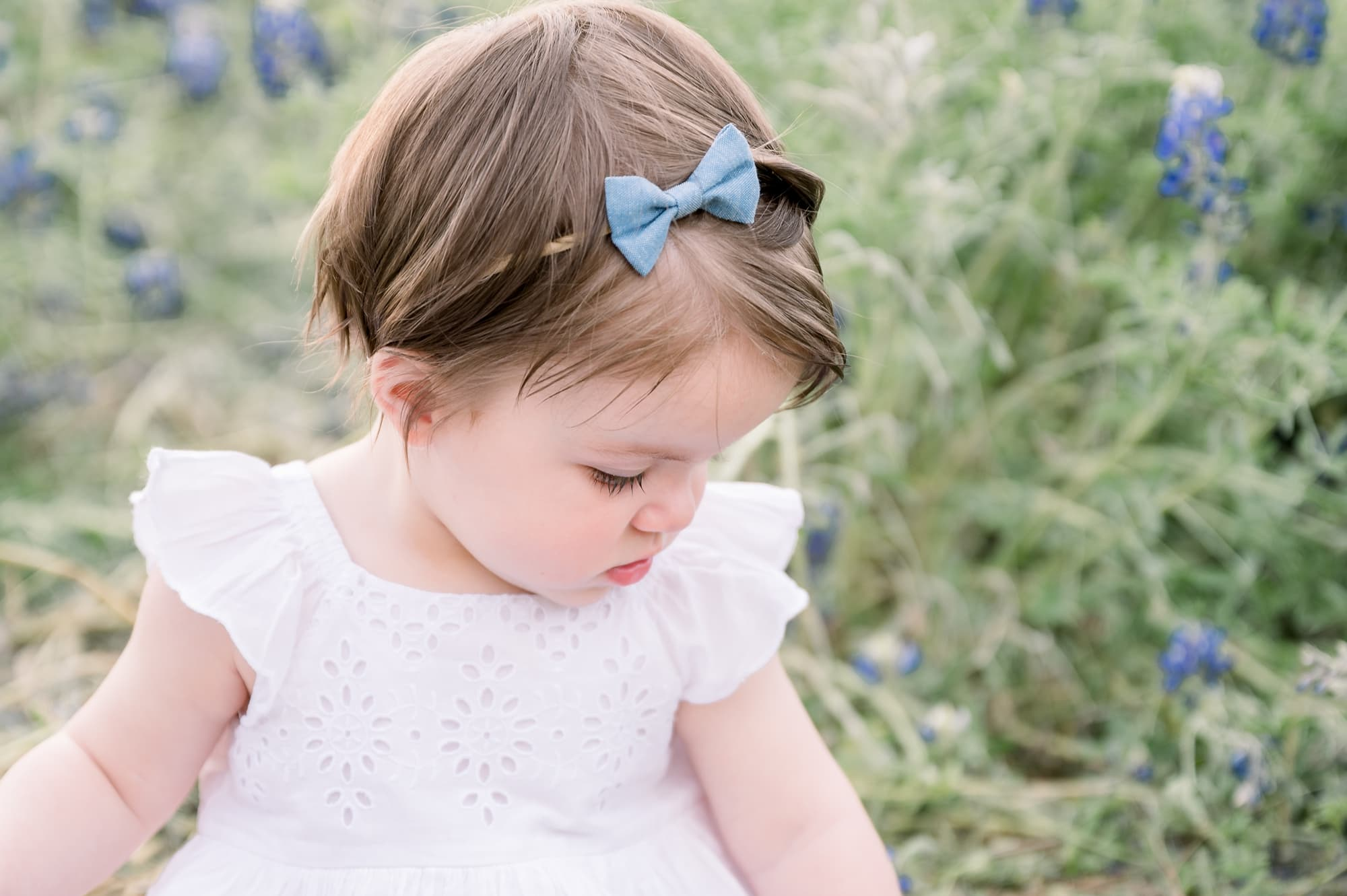 Closeup of baby girl wearing blue headband in field of bluebonnets. Photo by Aimee Hamilton Photography.