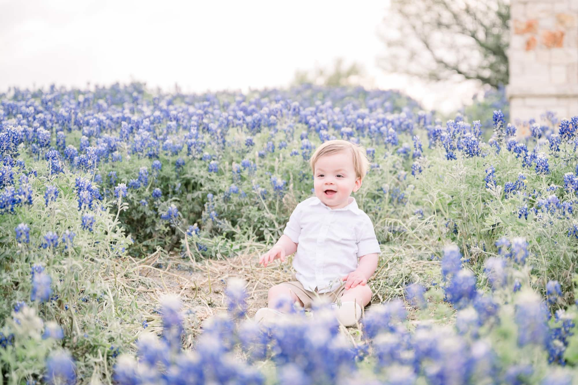Baby boy smiling during family session in bluebonnet field. Photo by Aimee Hamilton Photography.