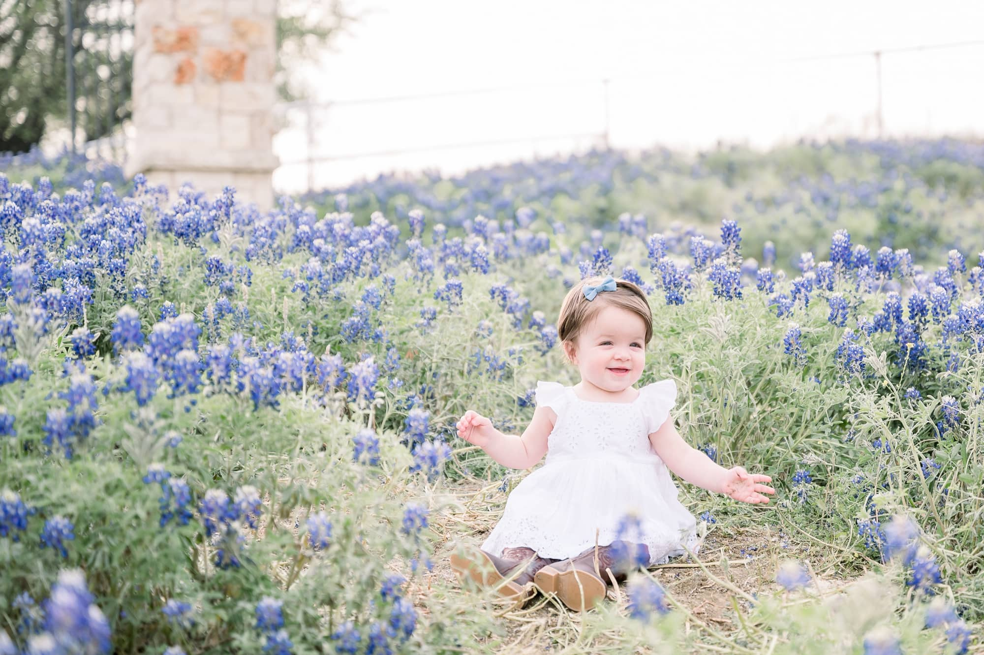 Baby girl smiling during family session in bluebonnet field by Prosper family photographer, Aimee Hamilton Photography.