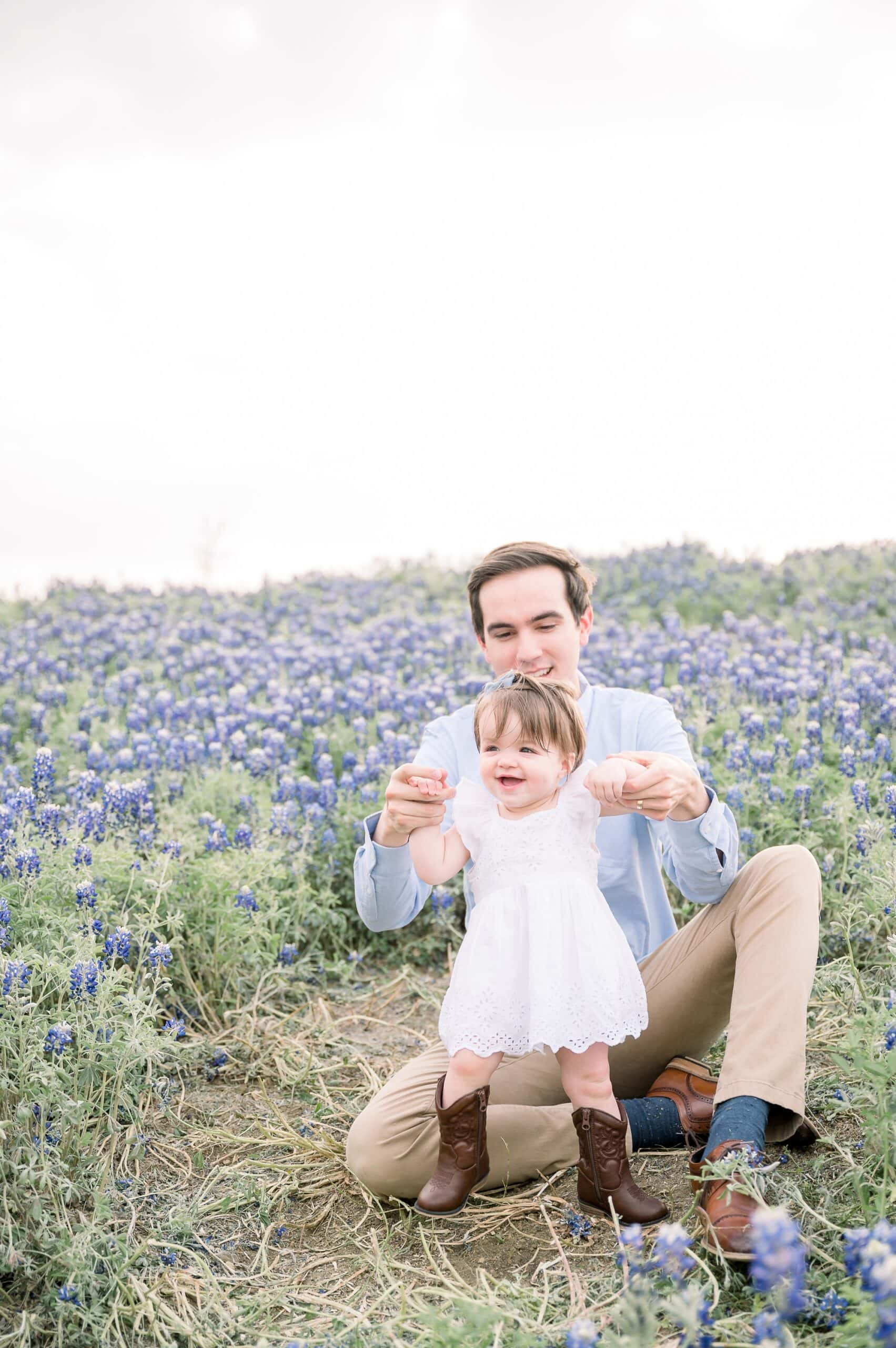 Closeup of Dad holding baby girl's hands in field of bluebonnet flowers in Texas. Photo by Prosper family photographer, Aimee Hamilton Photography.