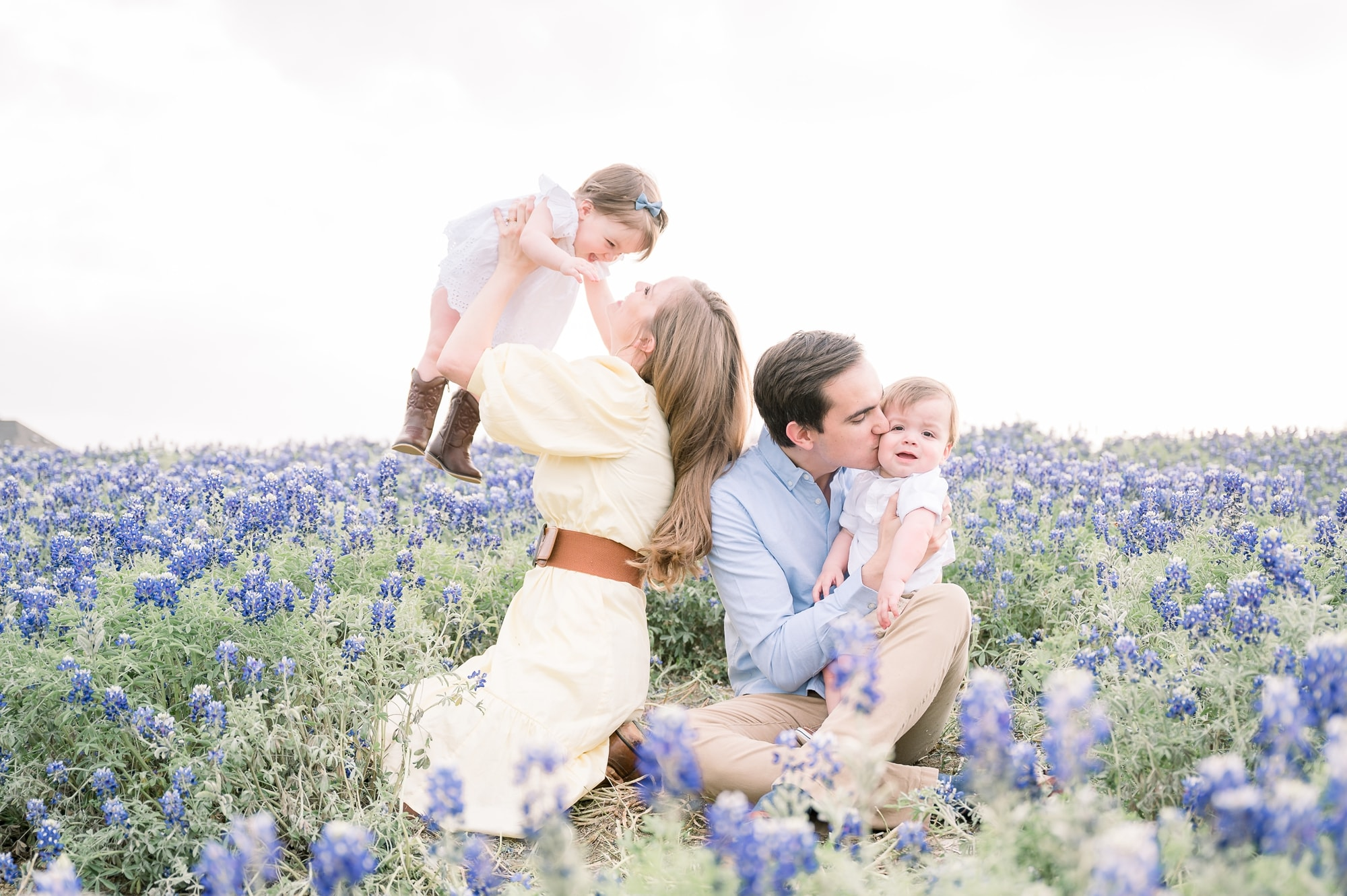 Parents playing and cuddling with twins in field of bluebonnet flowers. Photo by Prosper family photographer, Aimee Hamilton Photography.