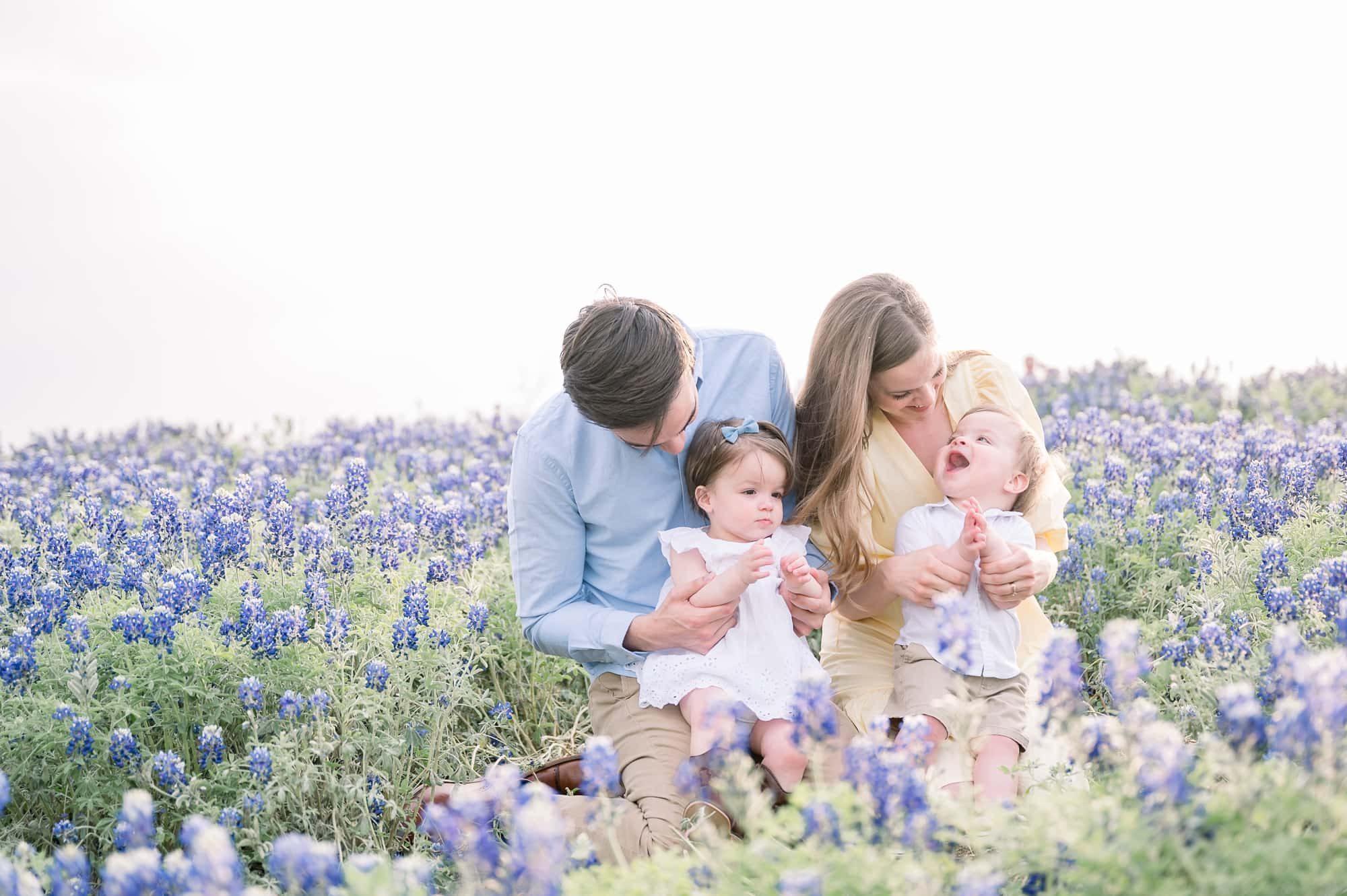 Mom and Dad sitting with twins in bluebonnet field. Photo by Aimee Hamilton Photography.