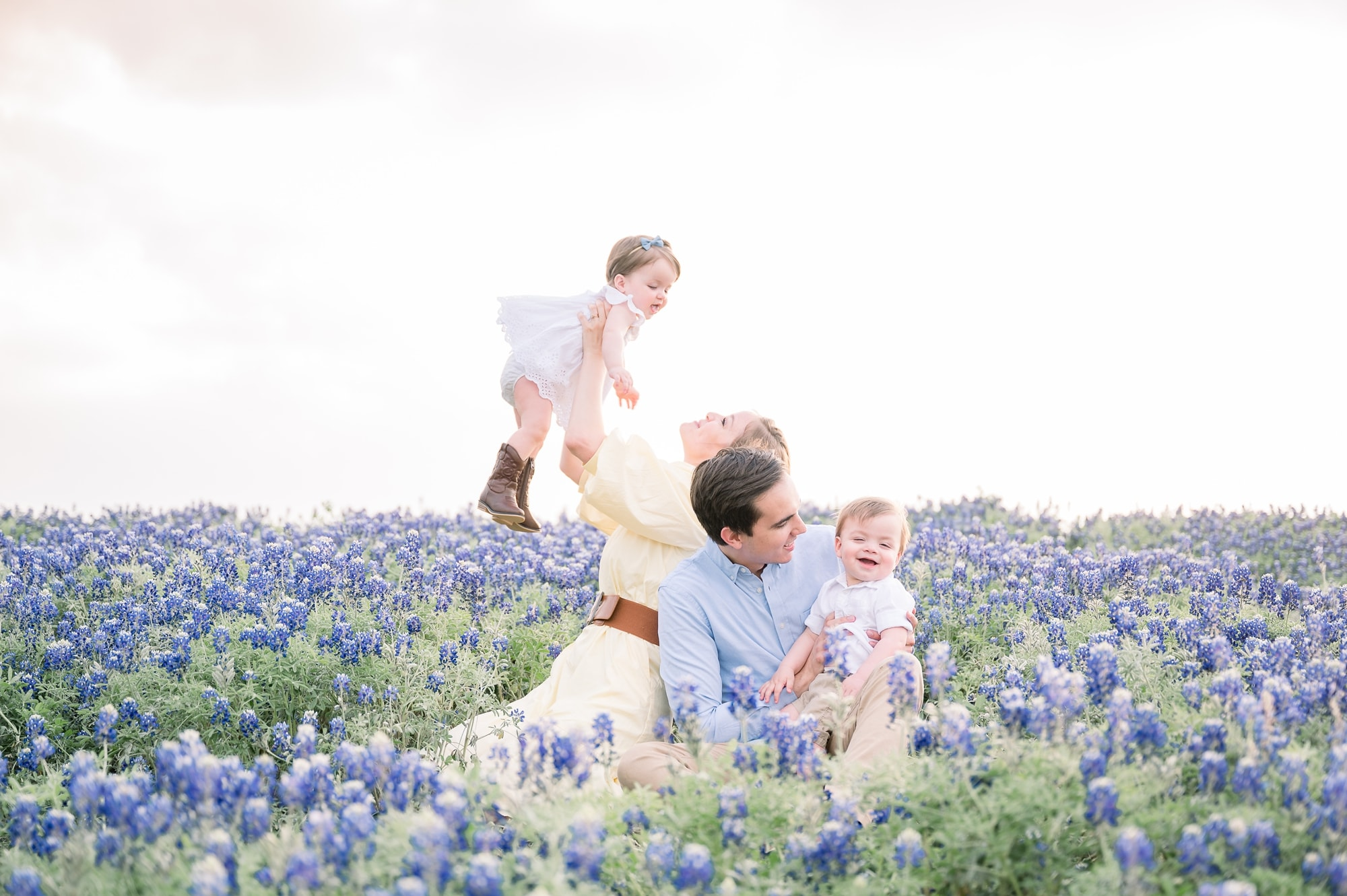 Mom and Dad playing with twins among the Texas bluebonnets. Photo by Prosper family photographer, Aimee Hamilton Photography.