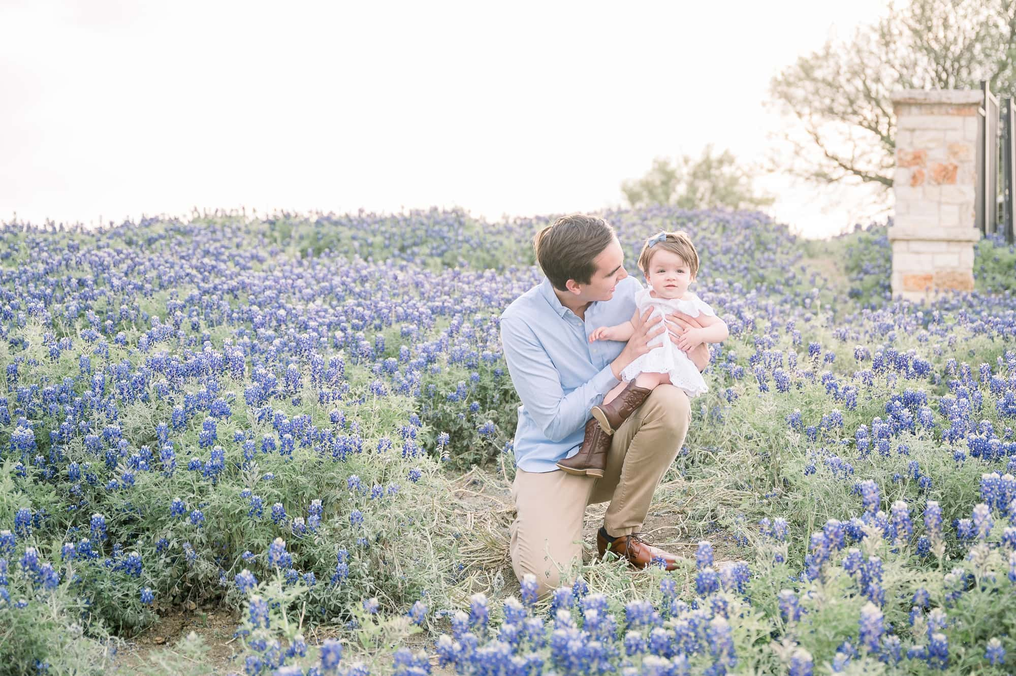 Dad kneels in bluebonnet field with toddler. Photo by Aimee Hamilton Photography.