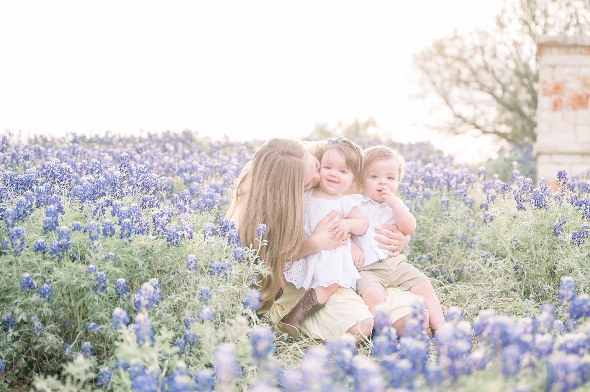 Mom kissing baby girl while twins sit on her lap in field of bluebonnets. Photo by Aimee Hamilton Photography.
