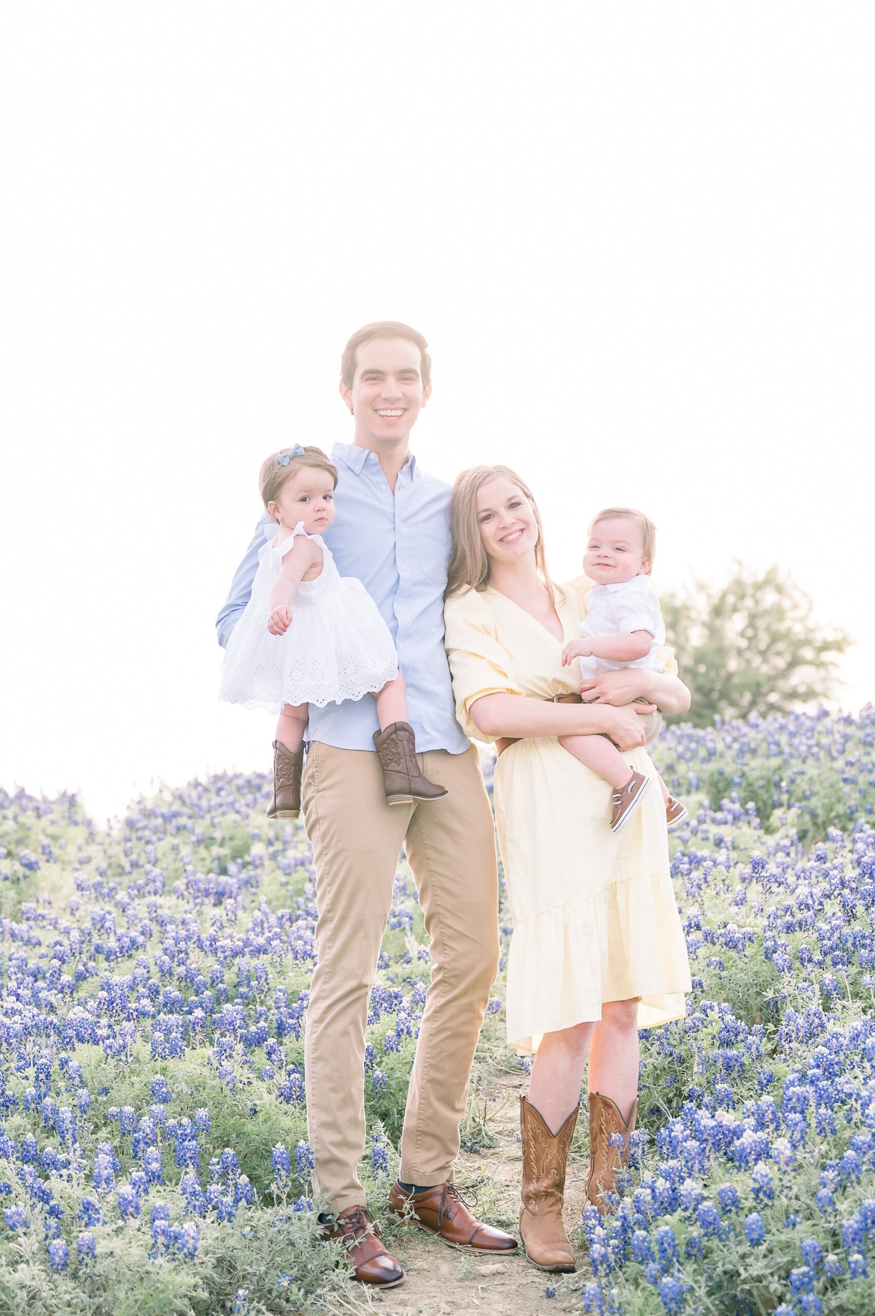 Family portrait with everyone smiling at the camera in bluebonnet field by Prosper family photographer, Aimee Hamilton Photography.
